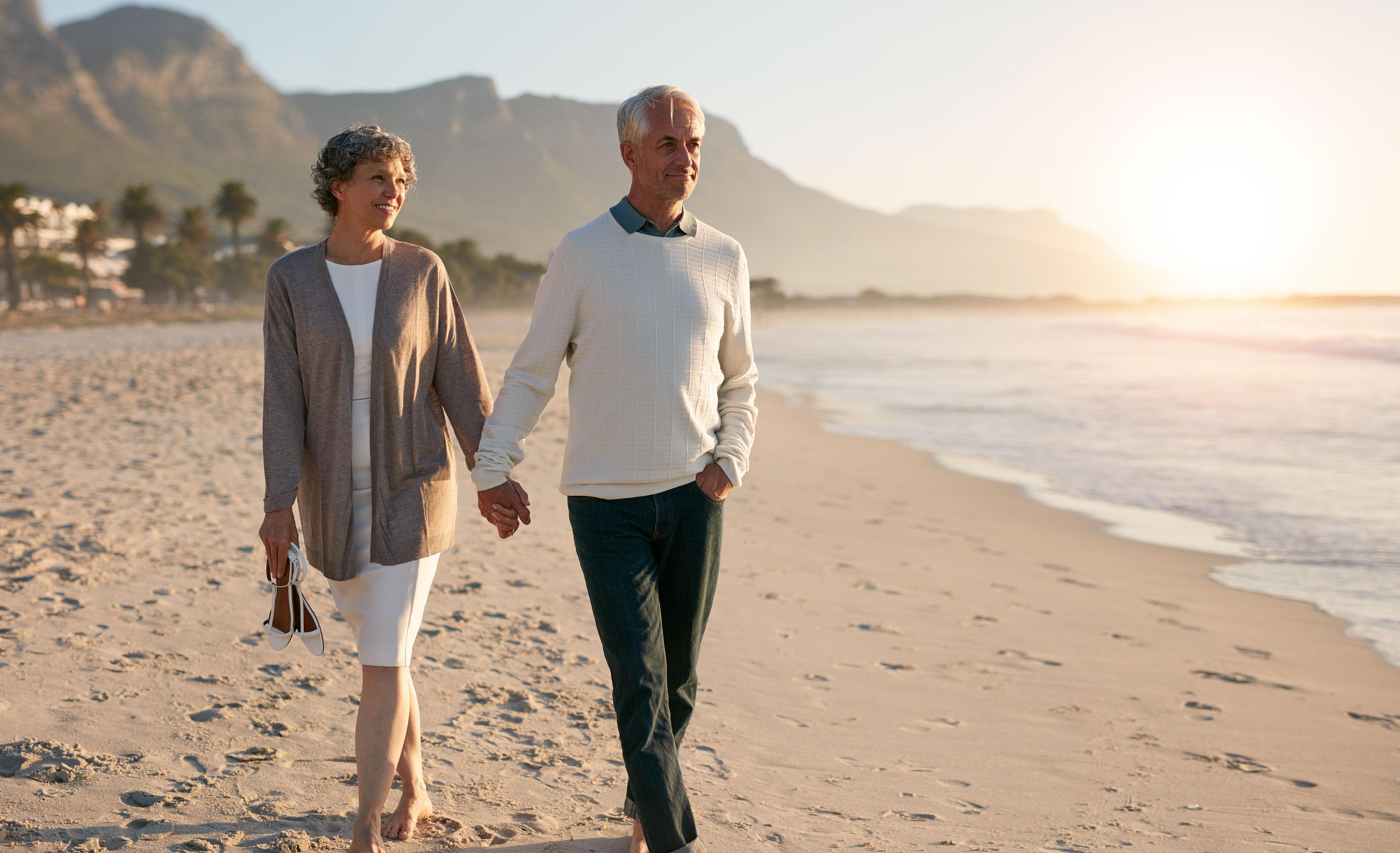 Älteres Paar macht entspannten Strandspaziergang