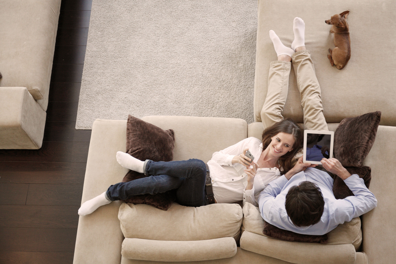 Paar auf Sofa liegend mit Tablet und Hund