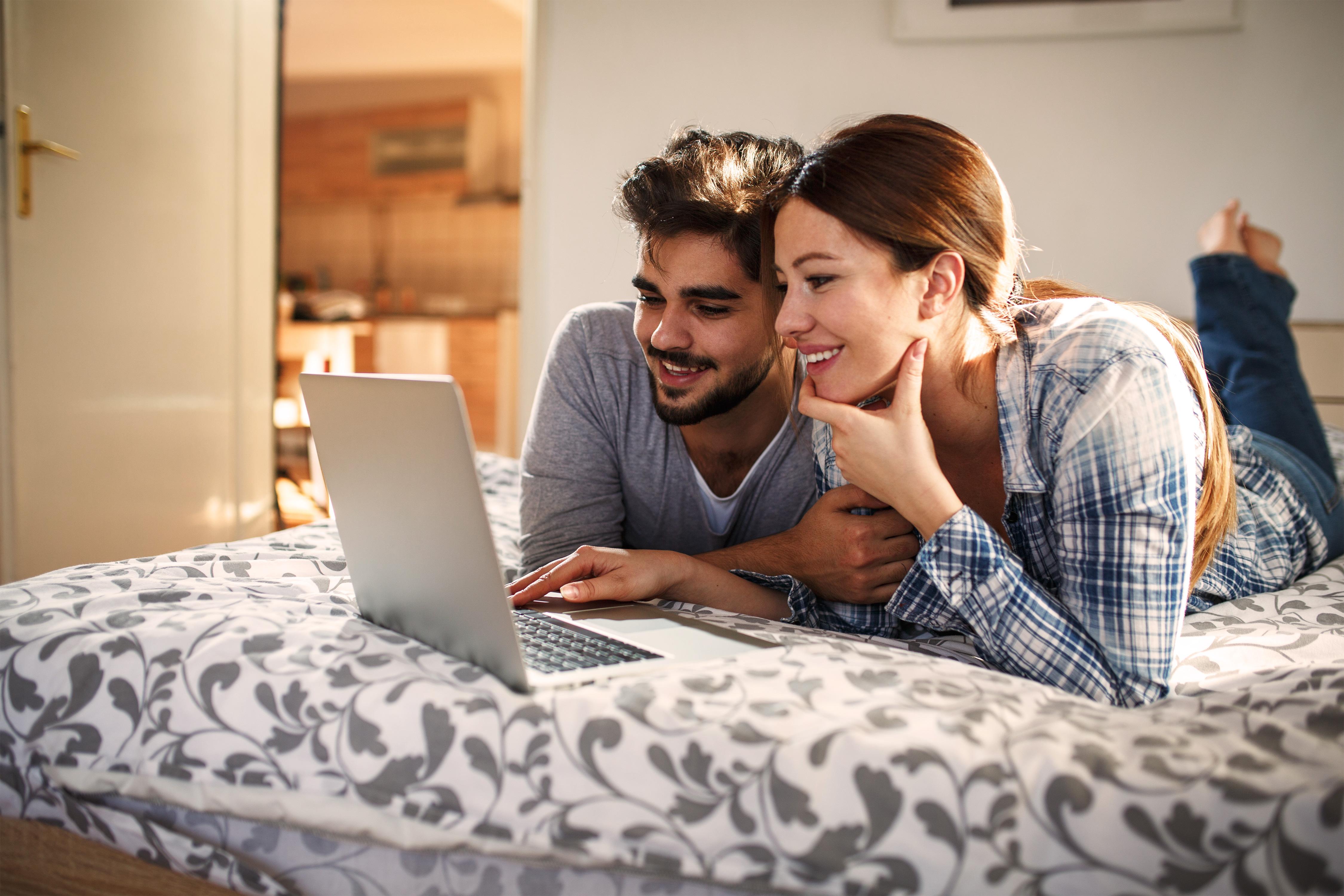 Junges lächelndes Paar auf dem Bett liegend vor dem Laptop