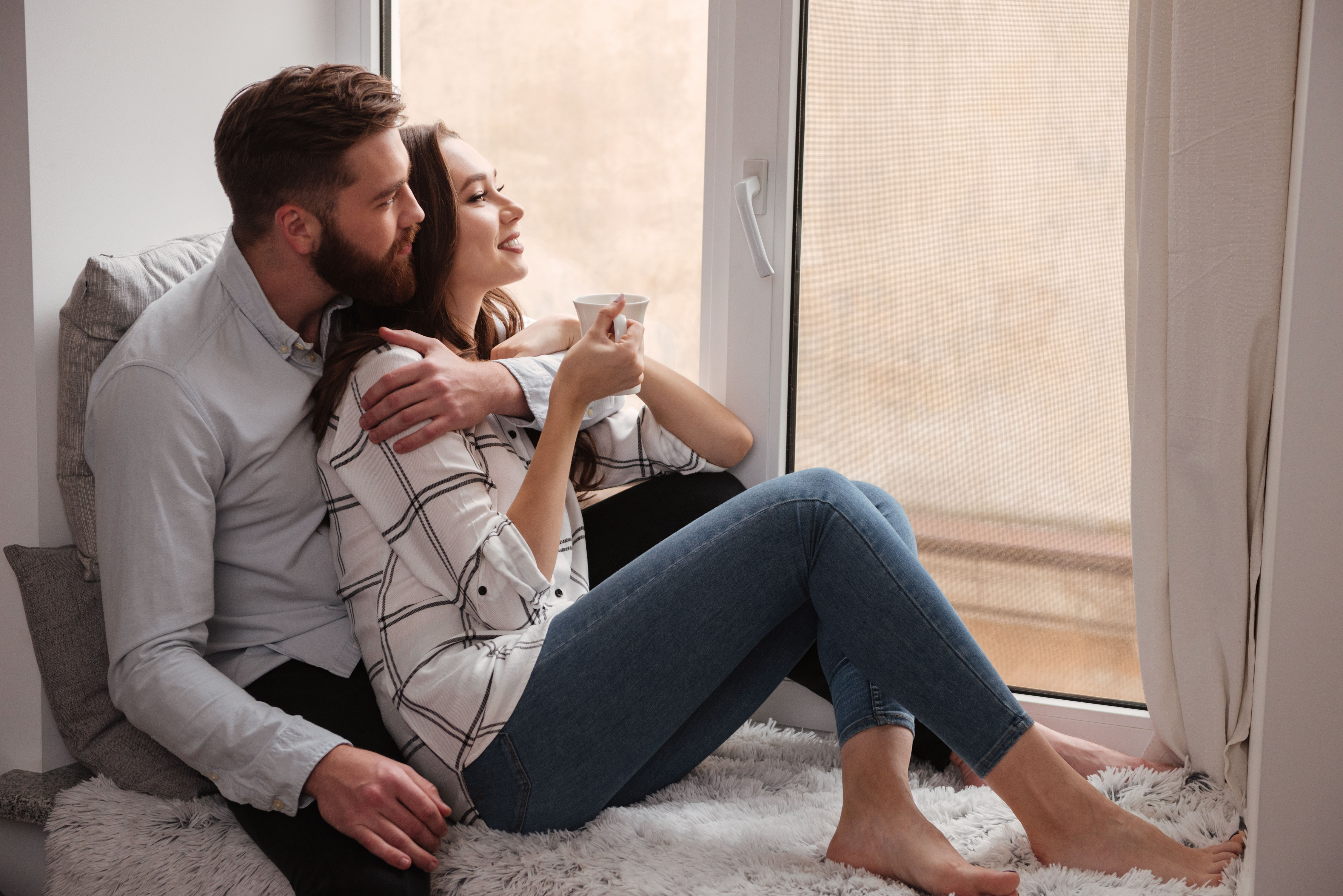 Junges Paar auf dem Boden sitzend sieht durchs geschlossene Fenster