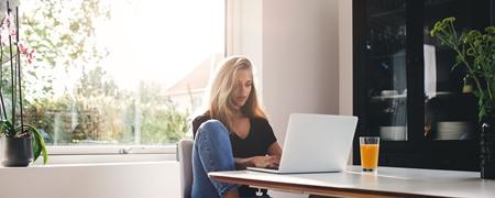 Junge Frau mit Laptop an Küchentisch