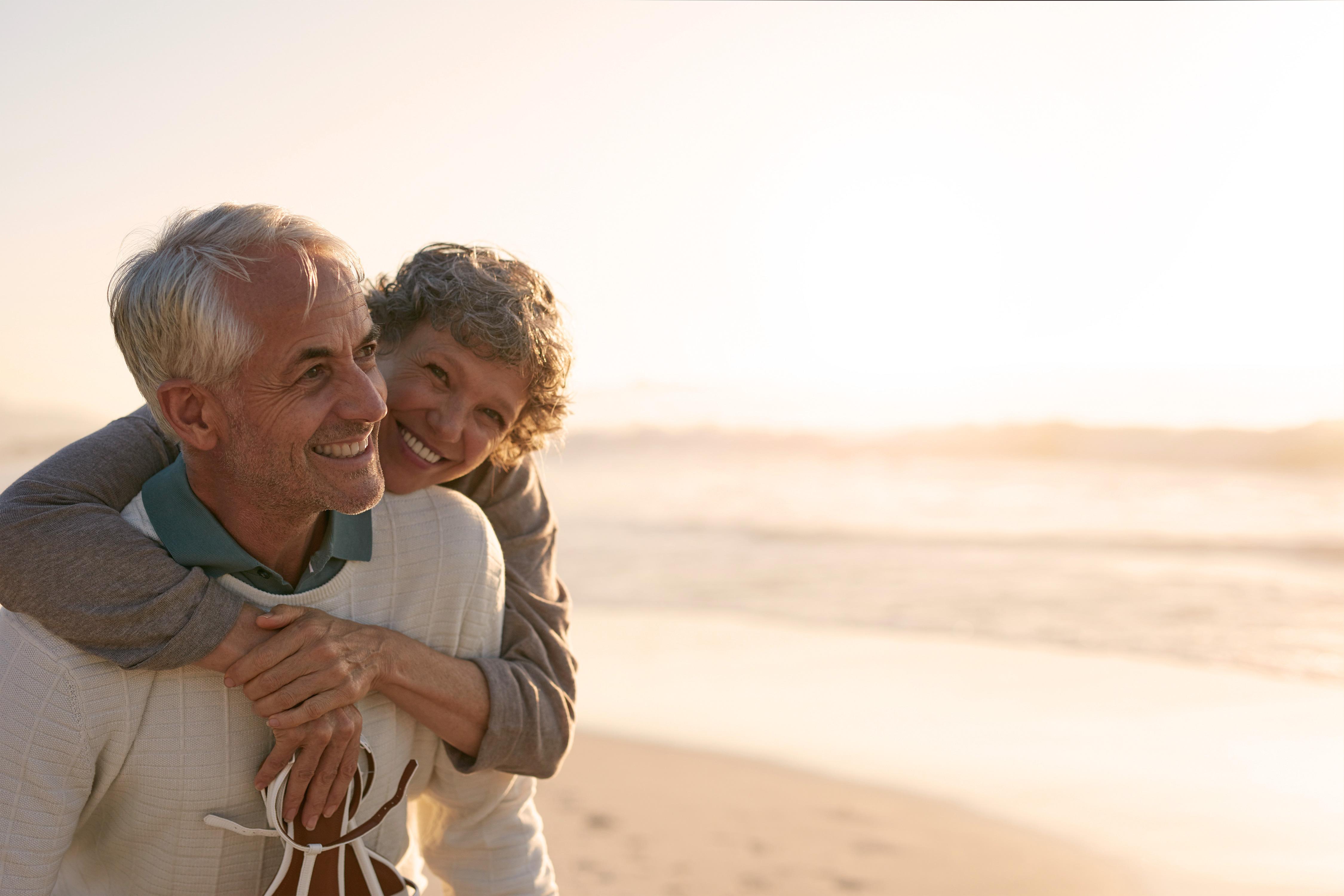 Älteres lächelndes Paar am Strand