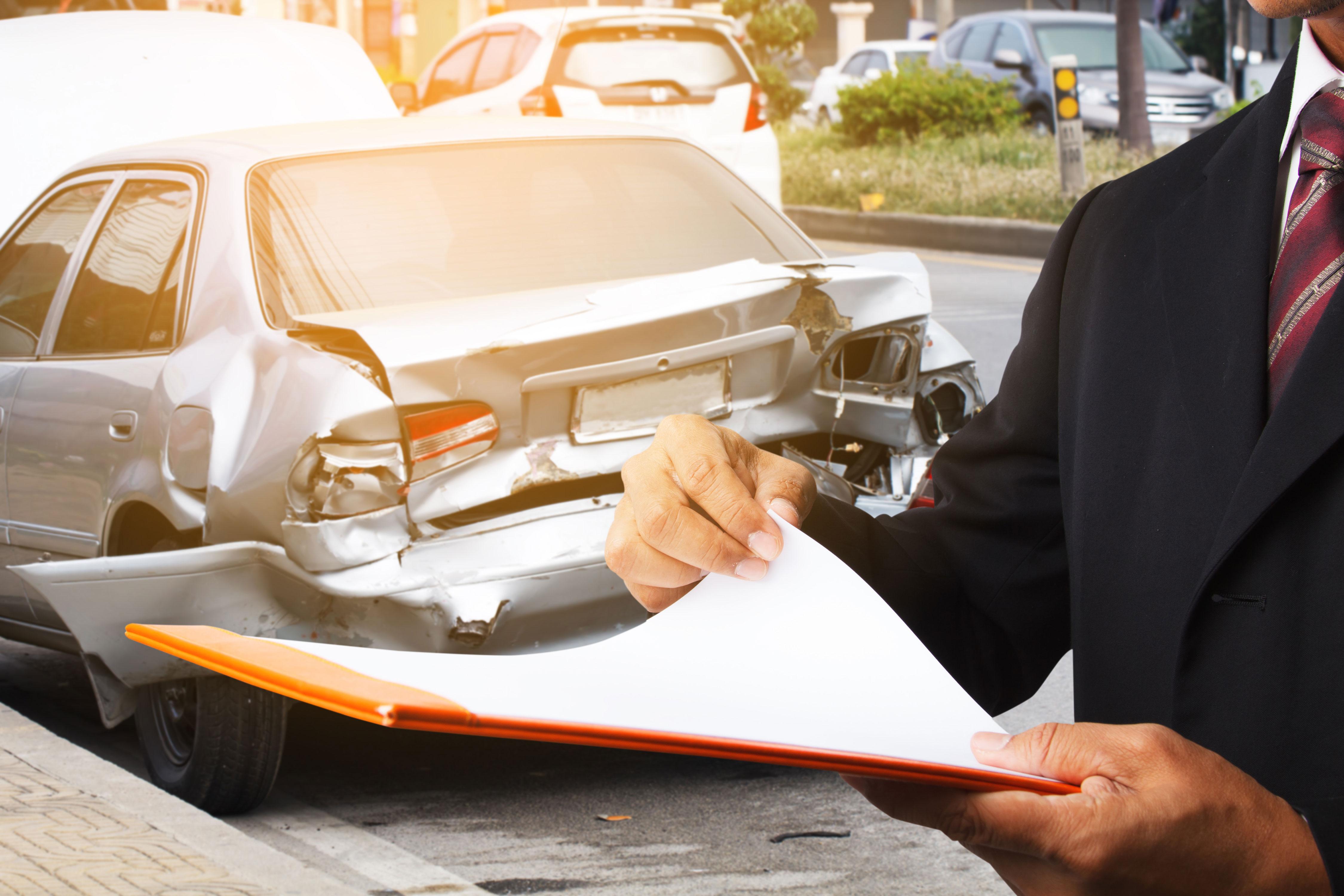 Versicherungsagent vor beschädigtem Auto mit Block in der Hand