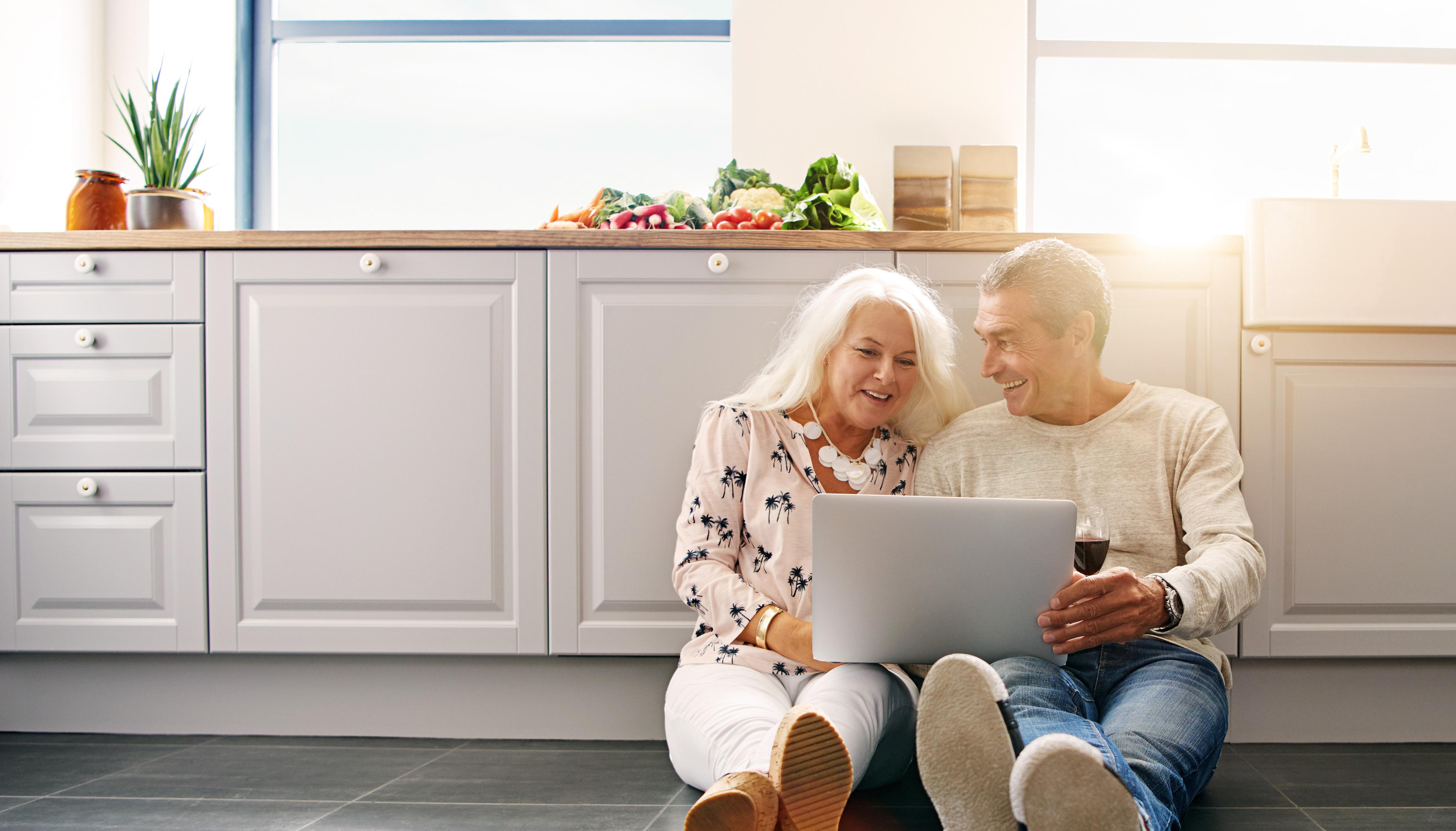 Älteres lächelndes Paar vor dem Laptop auf dem Küchenboden sitzend