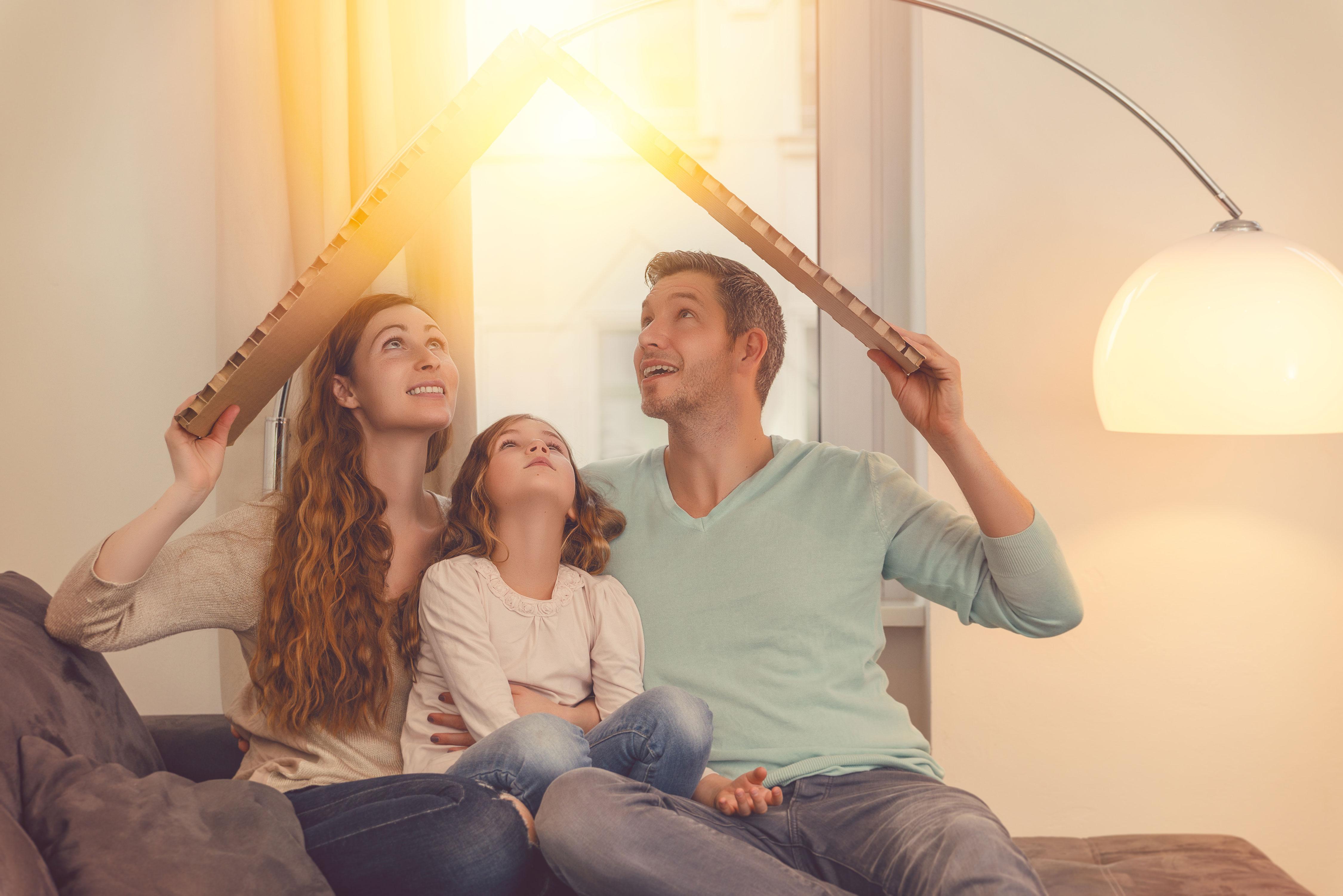 Junge Familie hält Pappkarton wie ein Dach schützend über sich