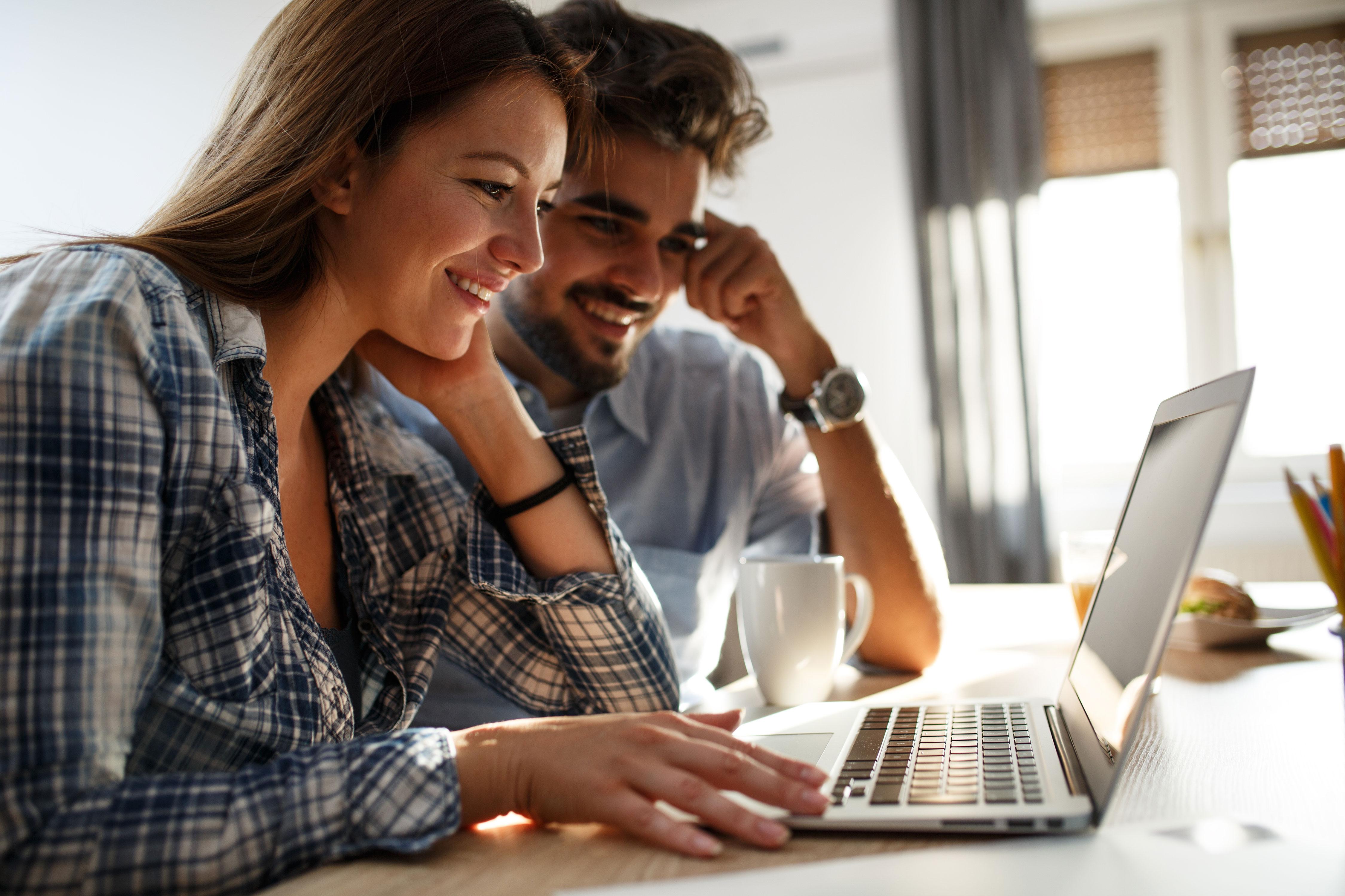Junges lächelndes Paar morgens am Küchentisch vor dem Laptop