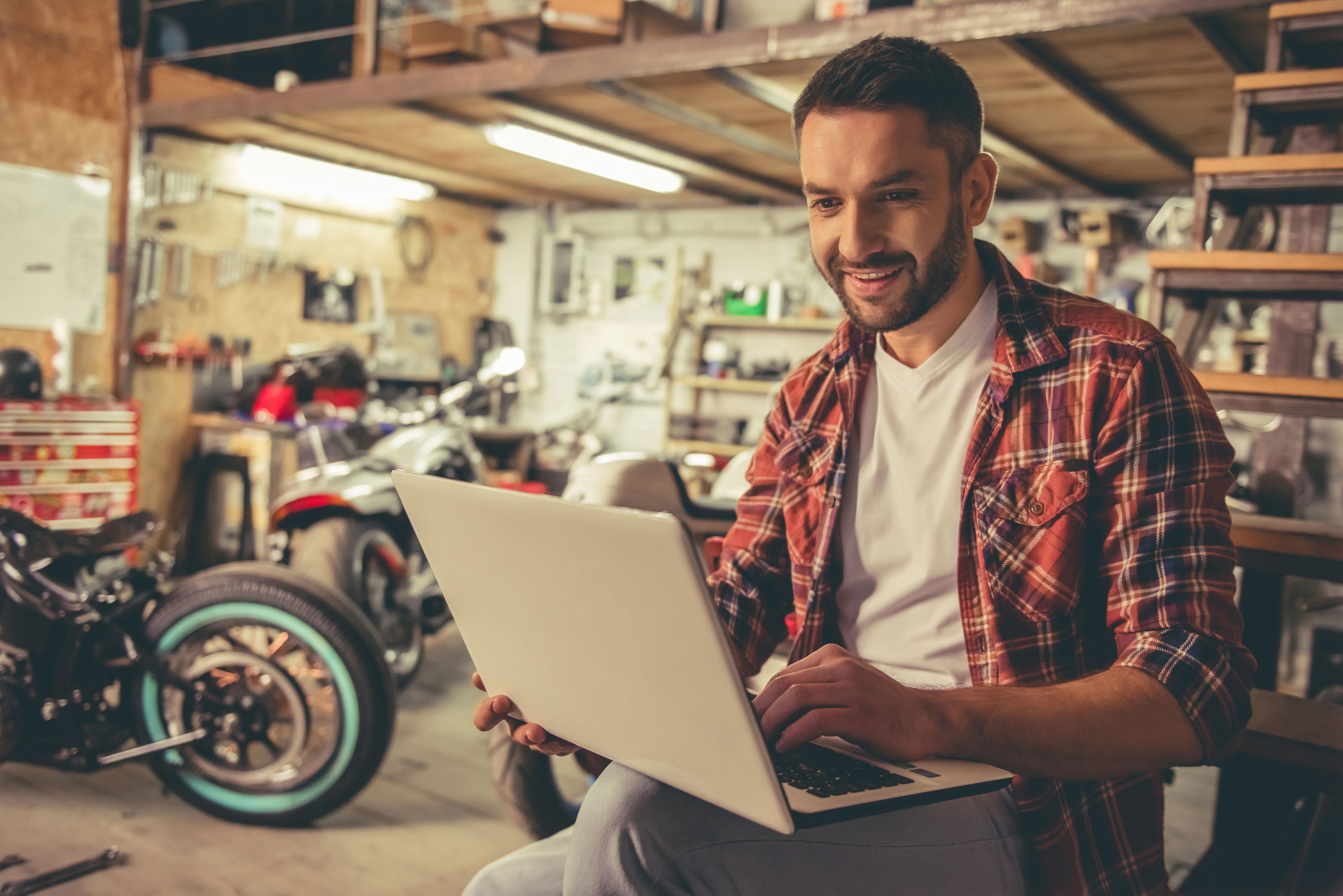 Mann mit Laptop auf dem Schoß in Motorradwerkstatt