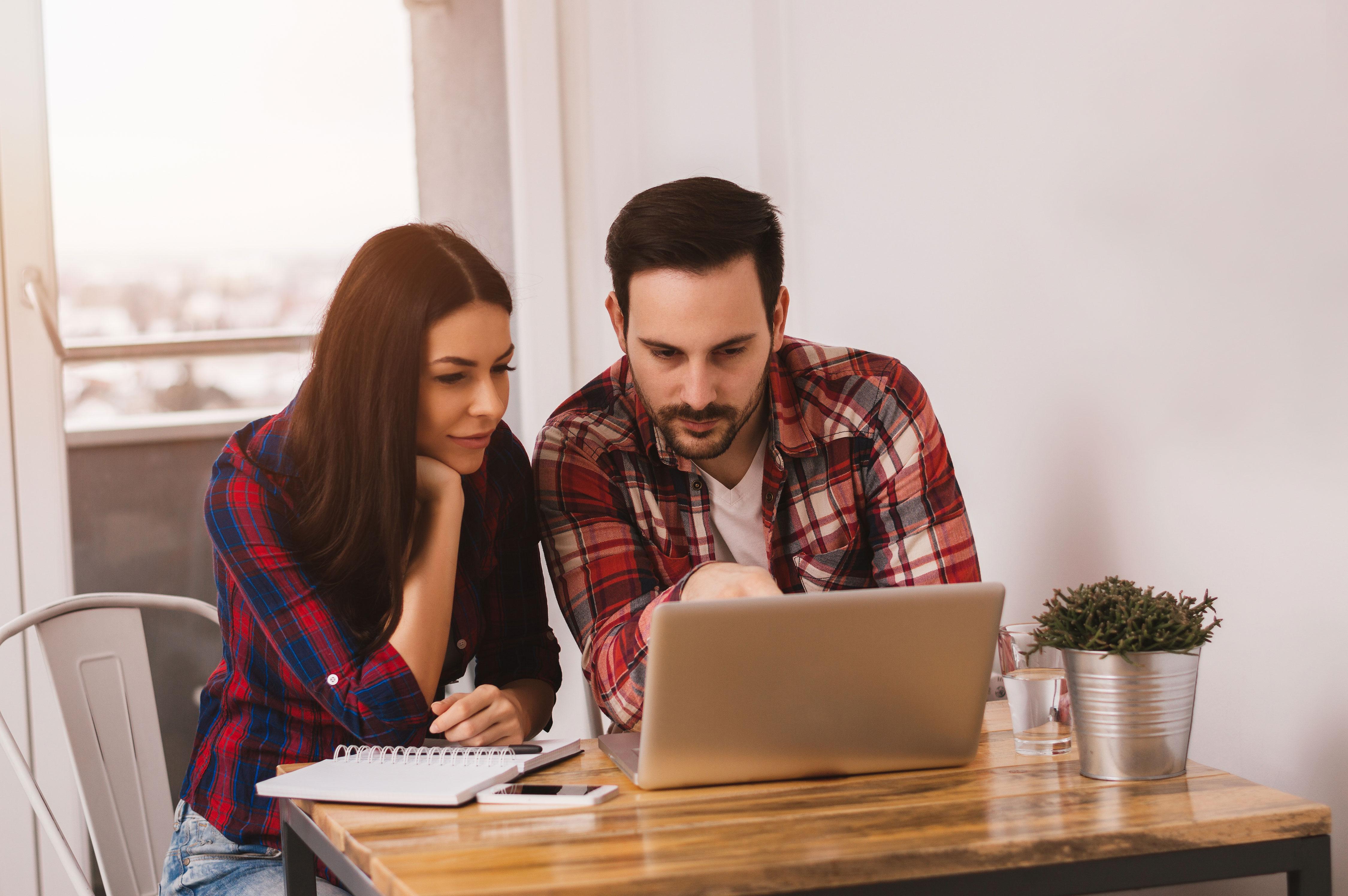 Junges Paar arbeitet gemeinsam an Laptop am Küchentisch