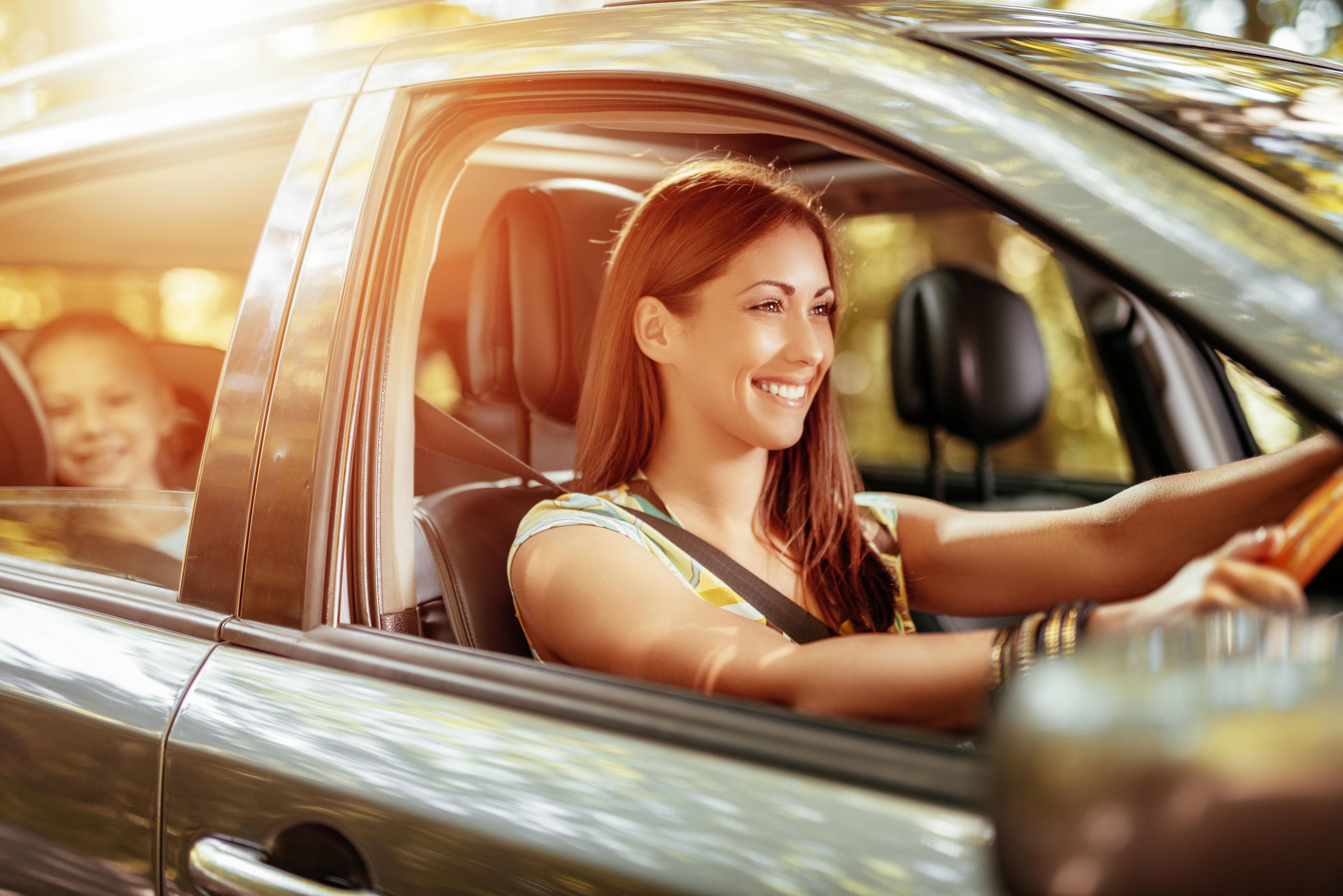 Mutter und Tochter lächelnd im Auto unterwegs