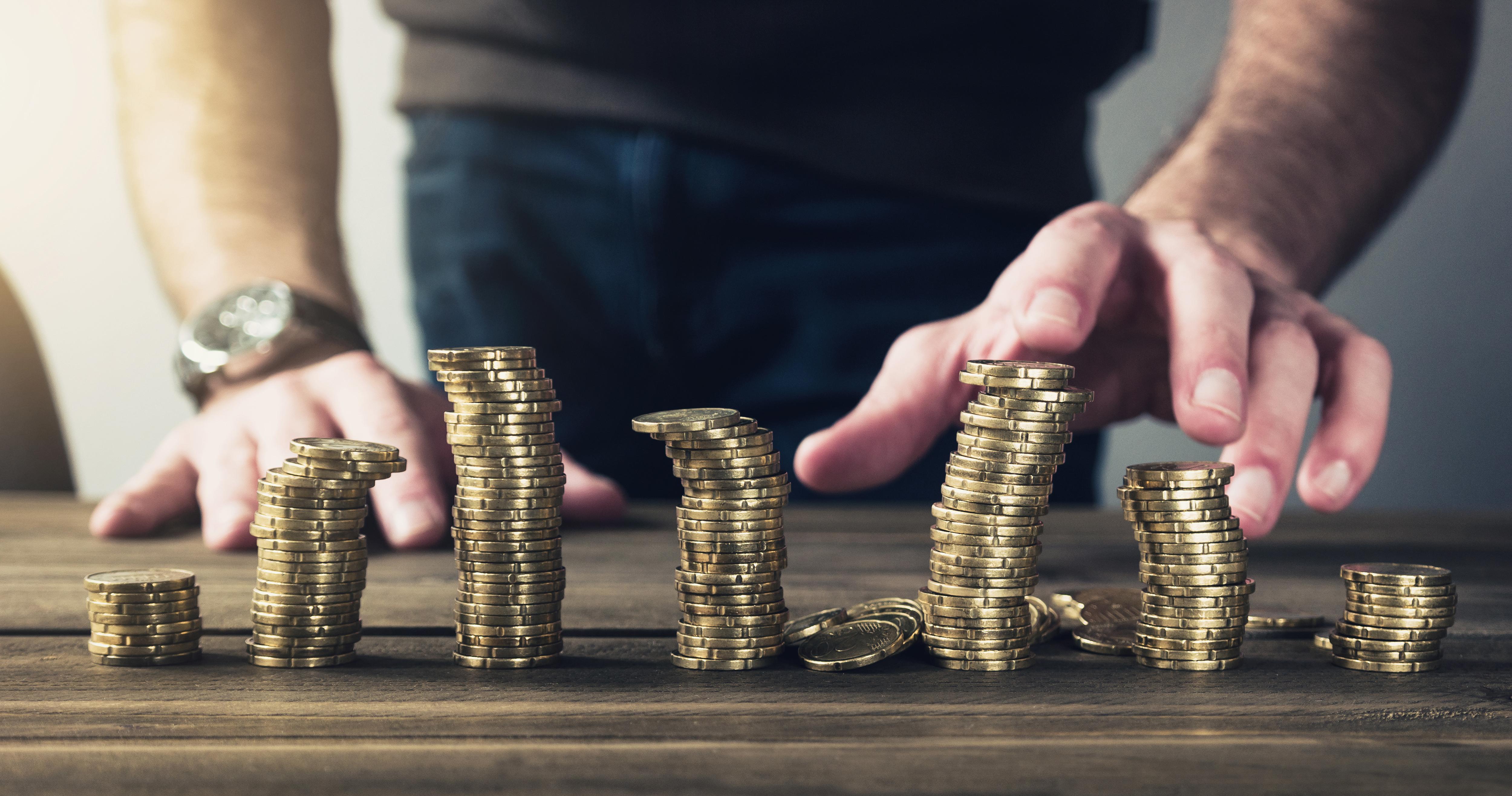 Mann stapelt Münzen auf Schreibtisch