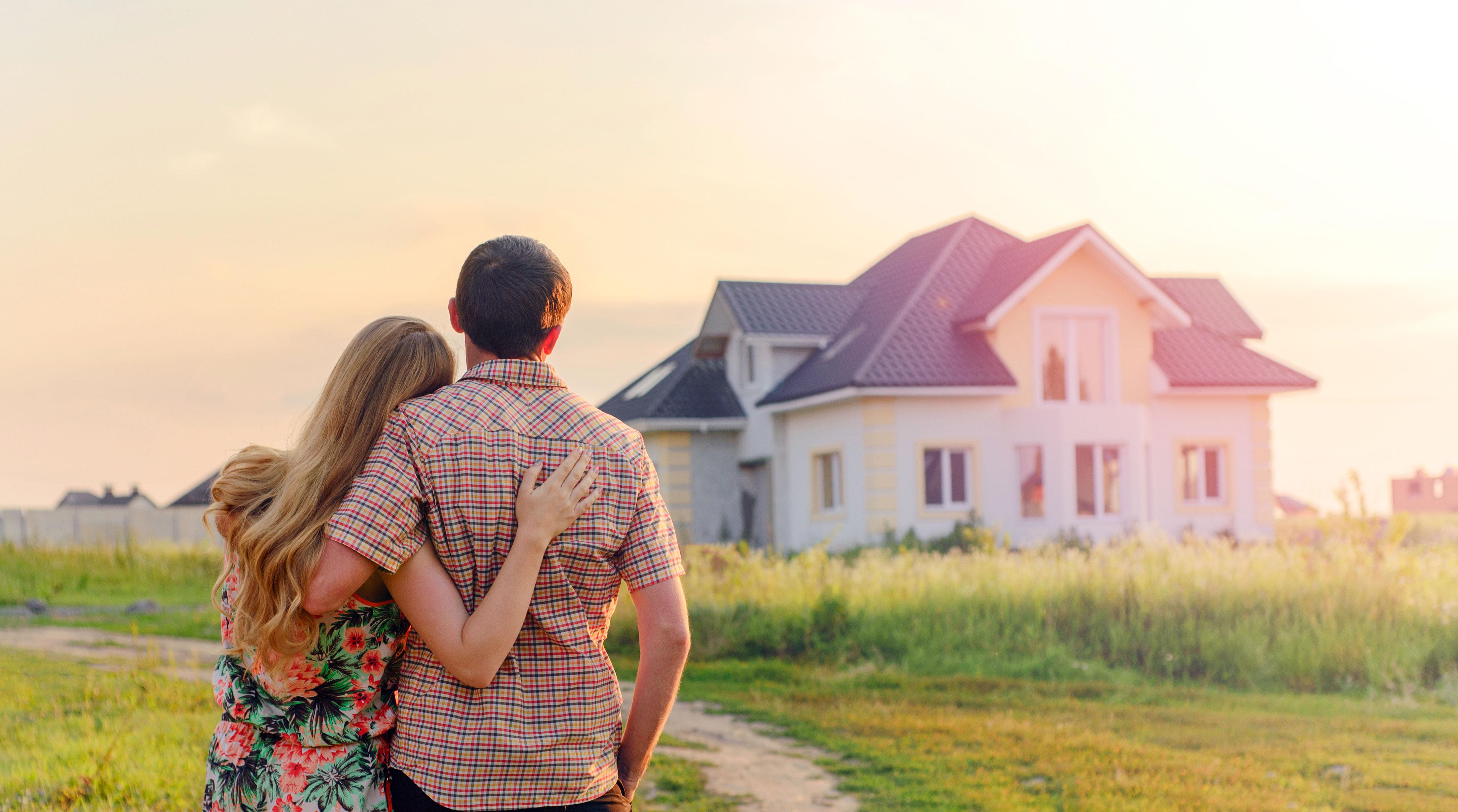 Junges Paar von hinten steht vor seinem Traumhaus