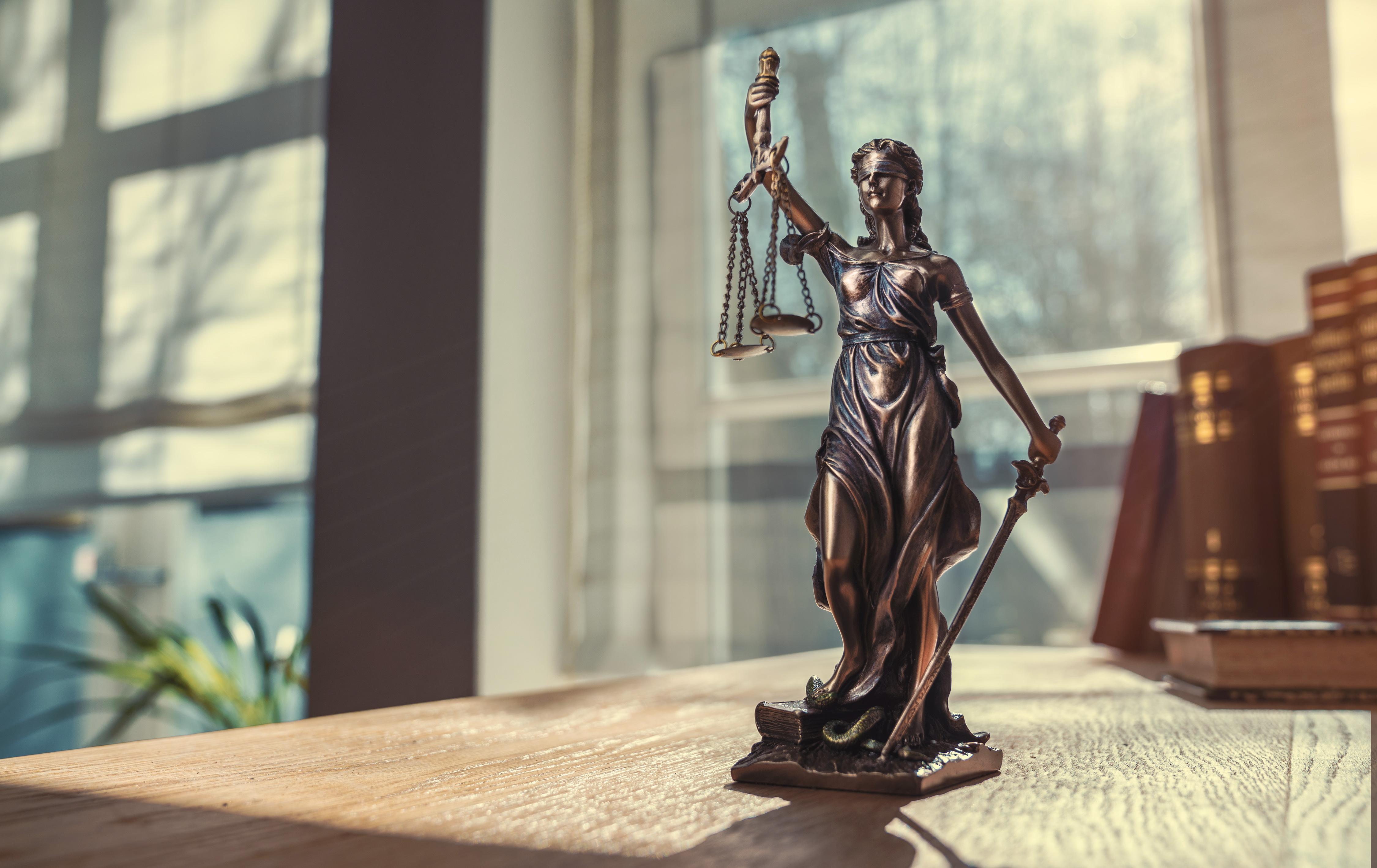 Justitia in Bronze auf einem Schreibtisch