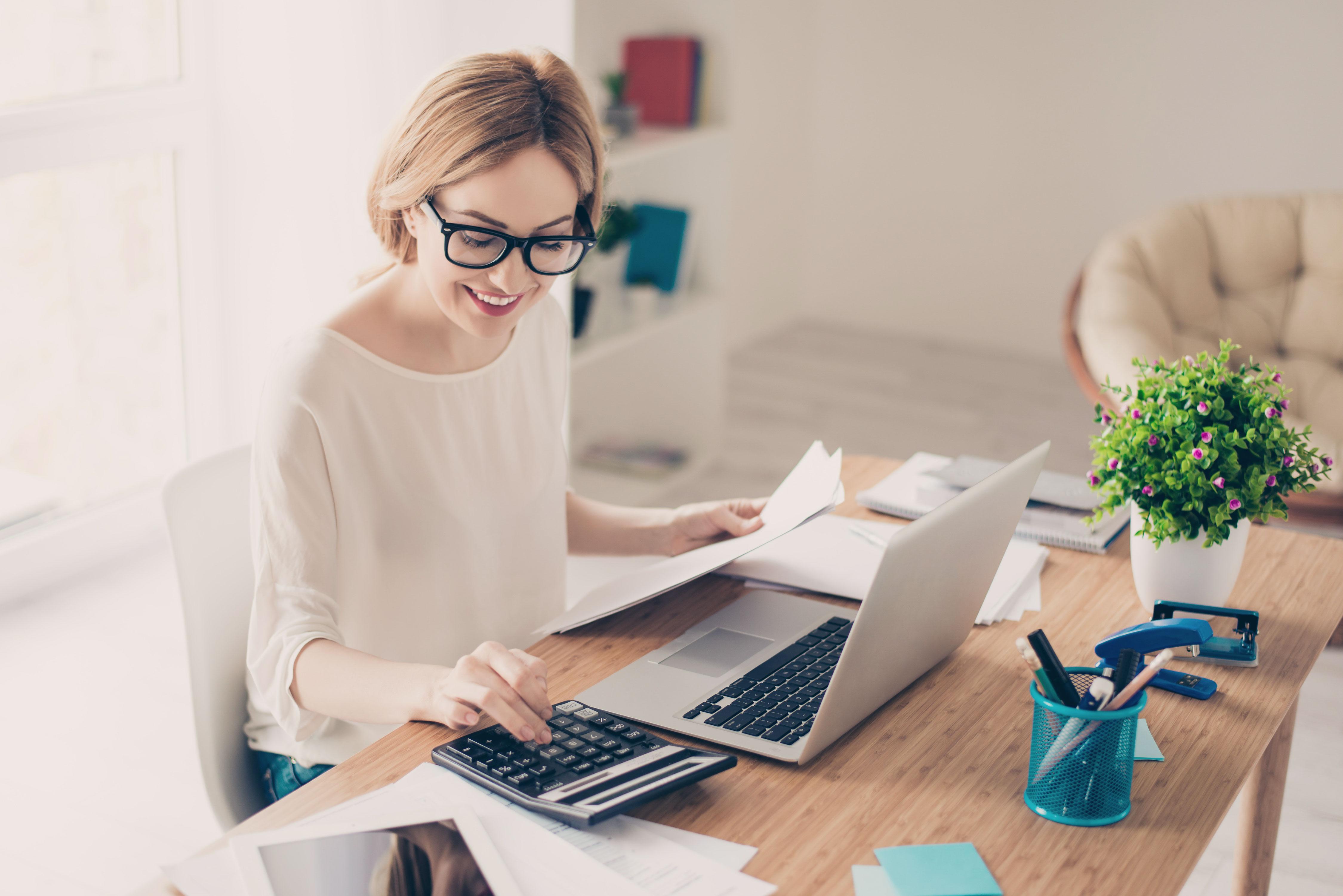 Lächelnde Junge Frau mit Taschenrechner, Dokumenten und Laptop am Schreibtisch
