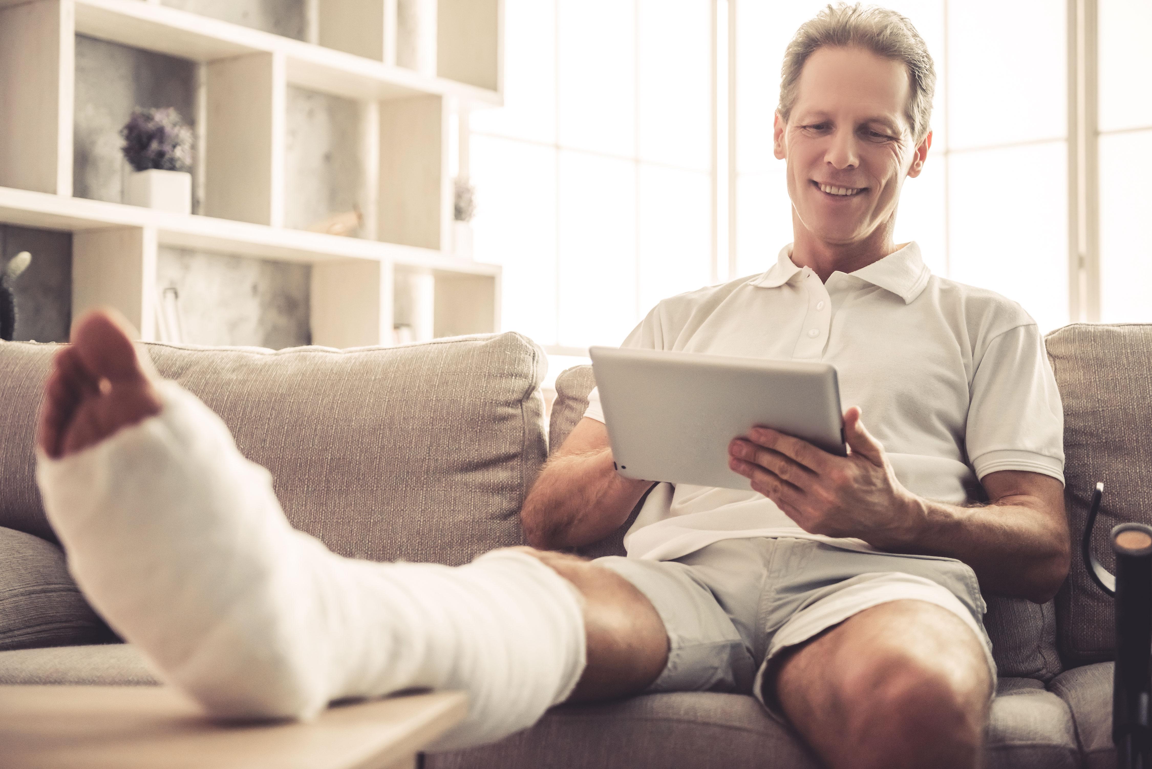 Mann mit gebrochenem Bein entspannt auf dem Sofa mit seinem Tablet
