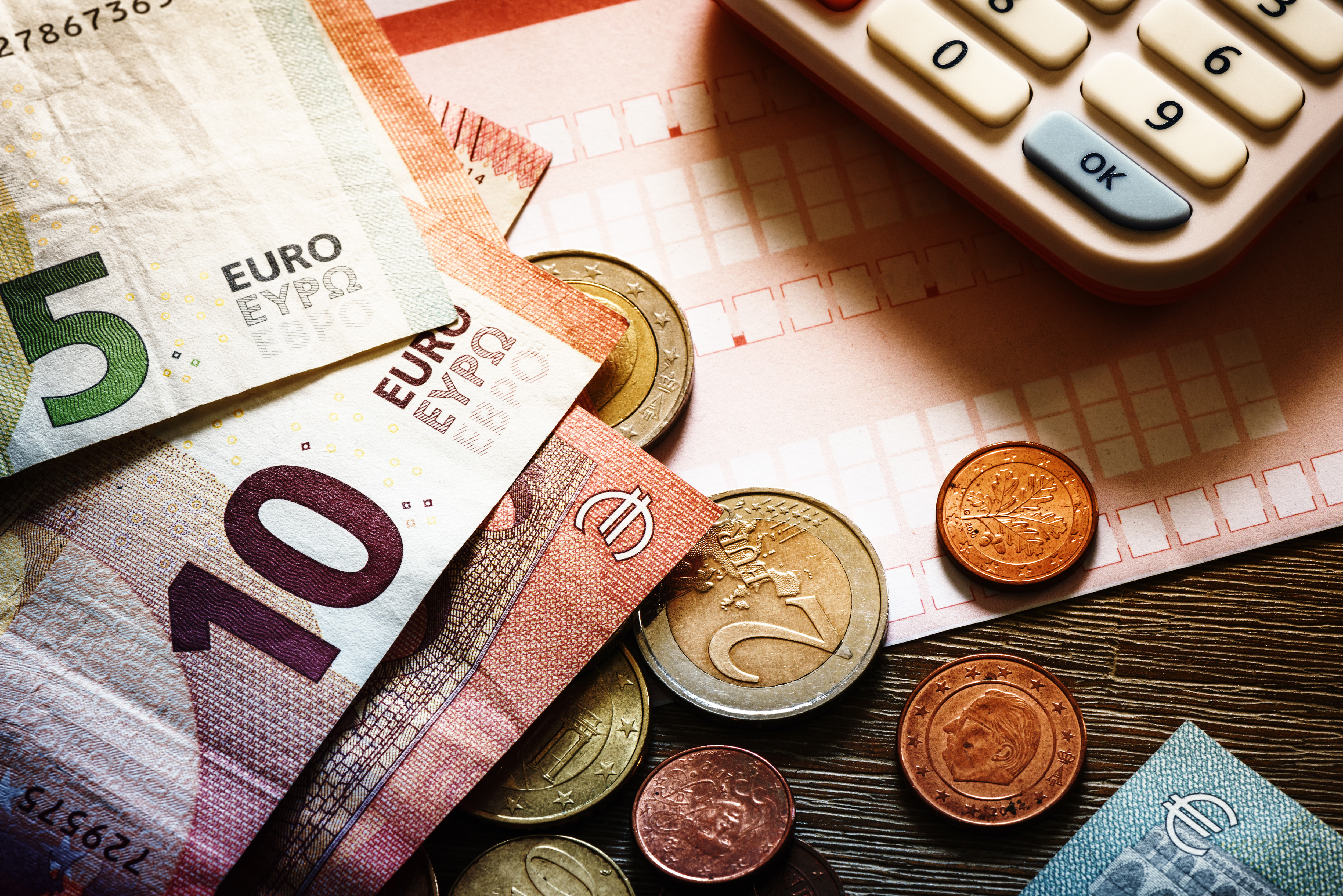 Euro-Banknoten und Münzen mit Rechnungen und Taschenrechner auf Holztisch