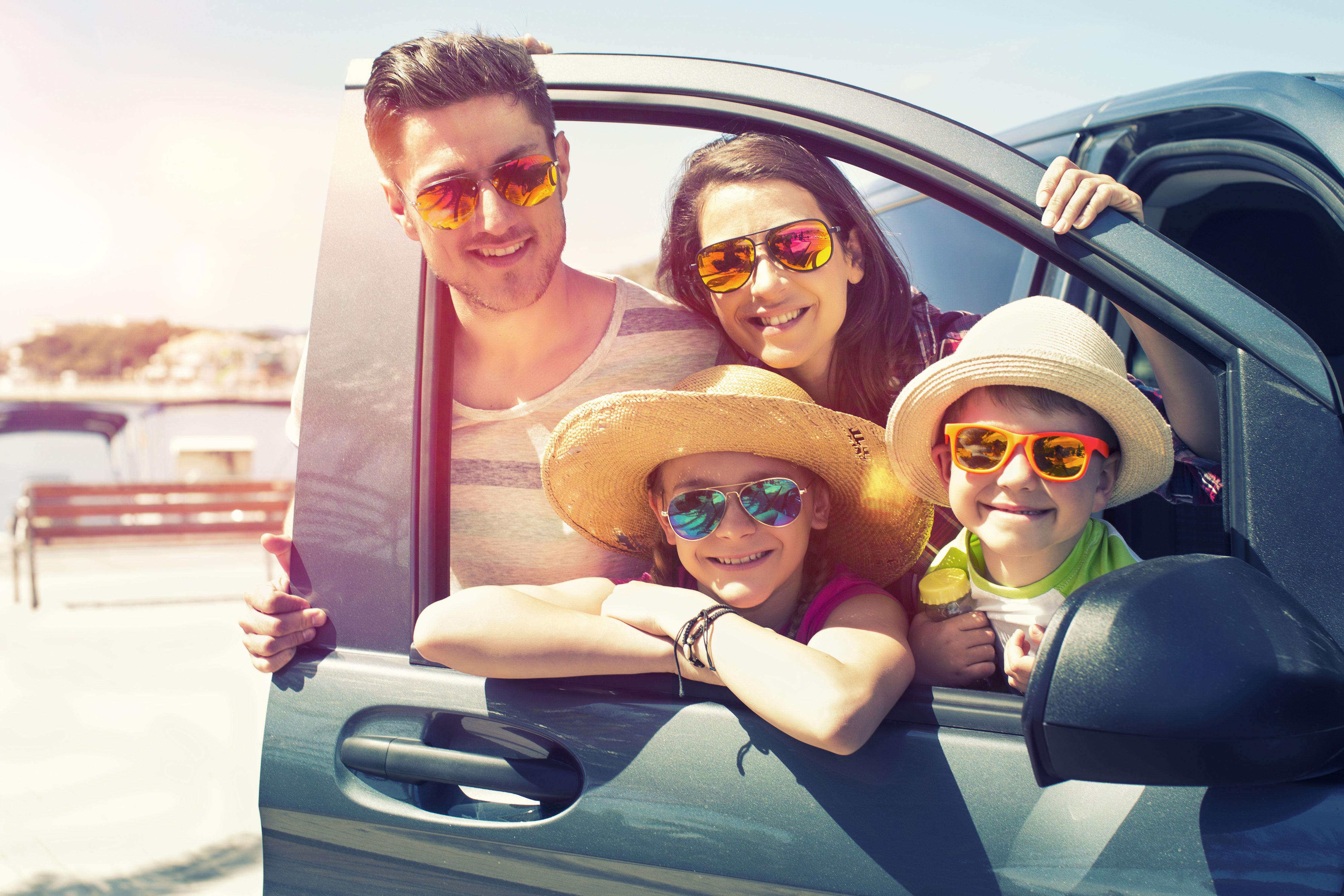 Familie mit Kindern mit Sonnenbrillen beim Familienausflug am Auto