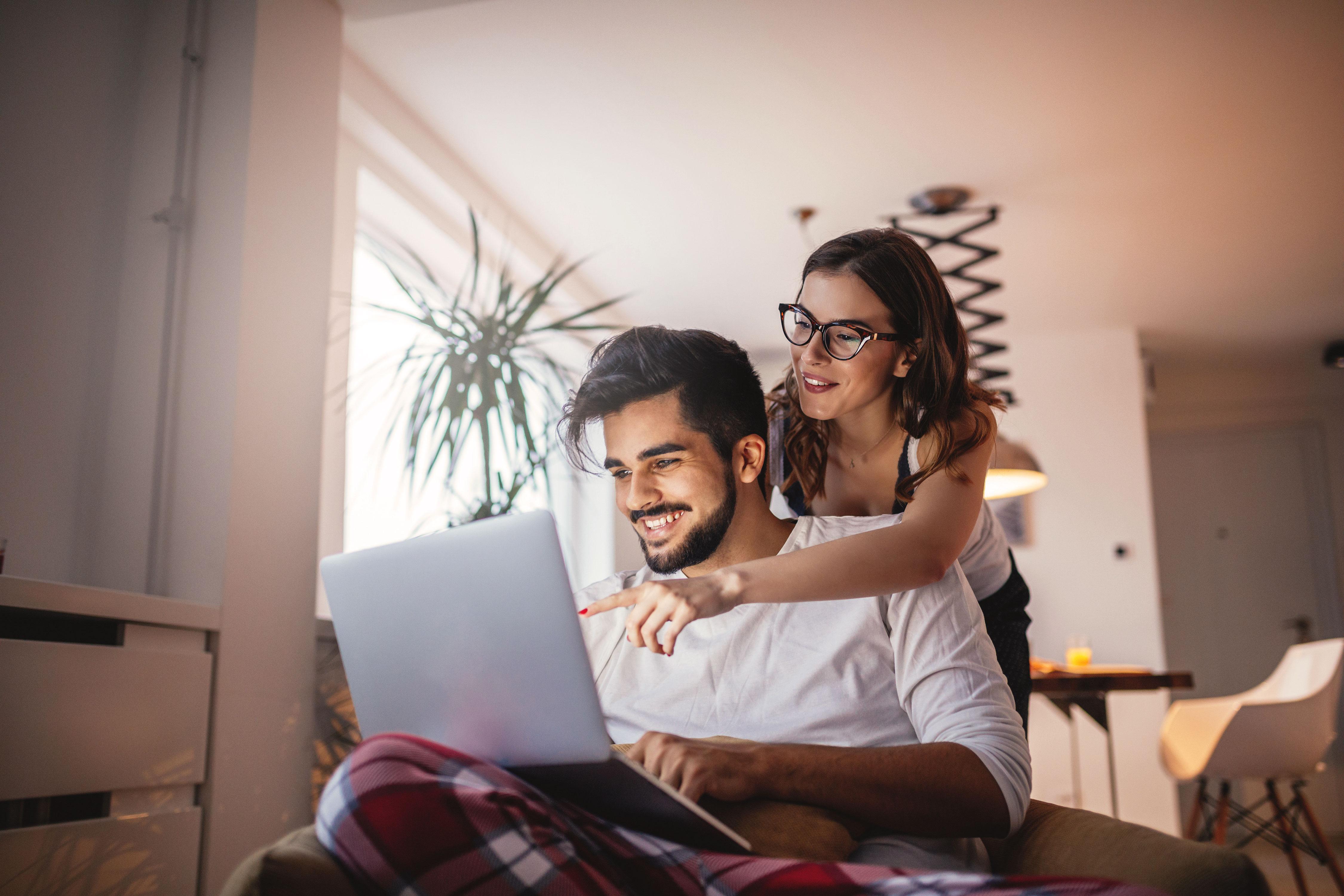 Lächelndes Paar vor Laptop auf Sofa