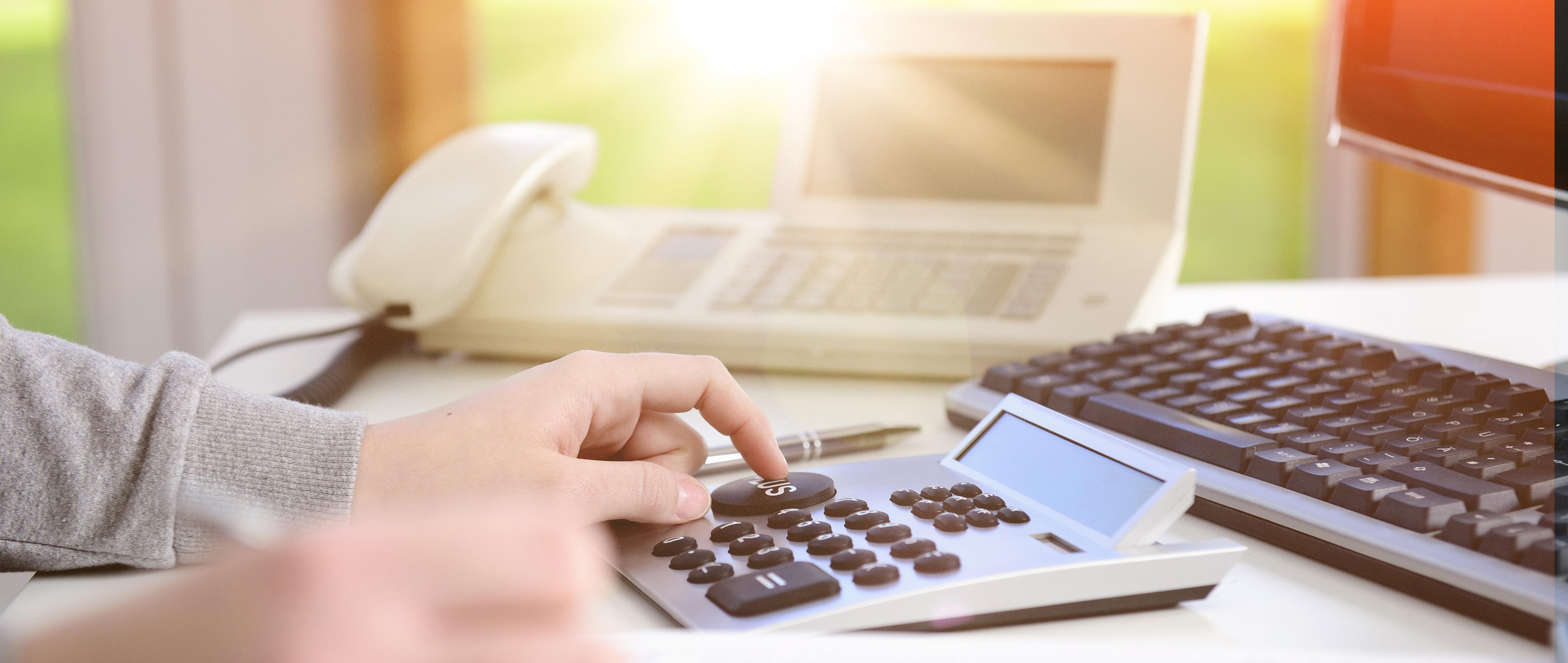 Frau kalkuliert mit Taschenrechner Umsatzsteuer mit Flares