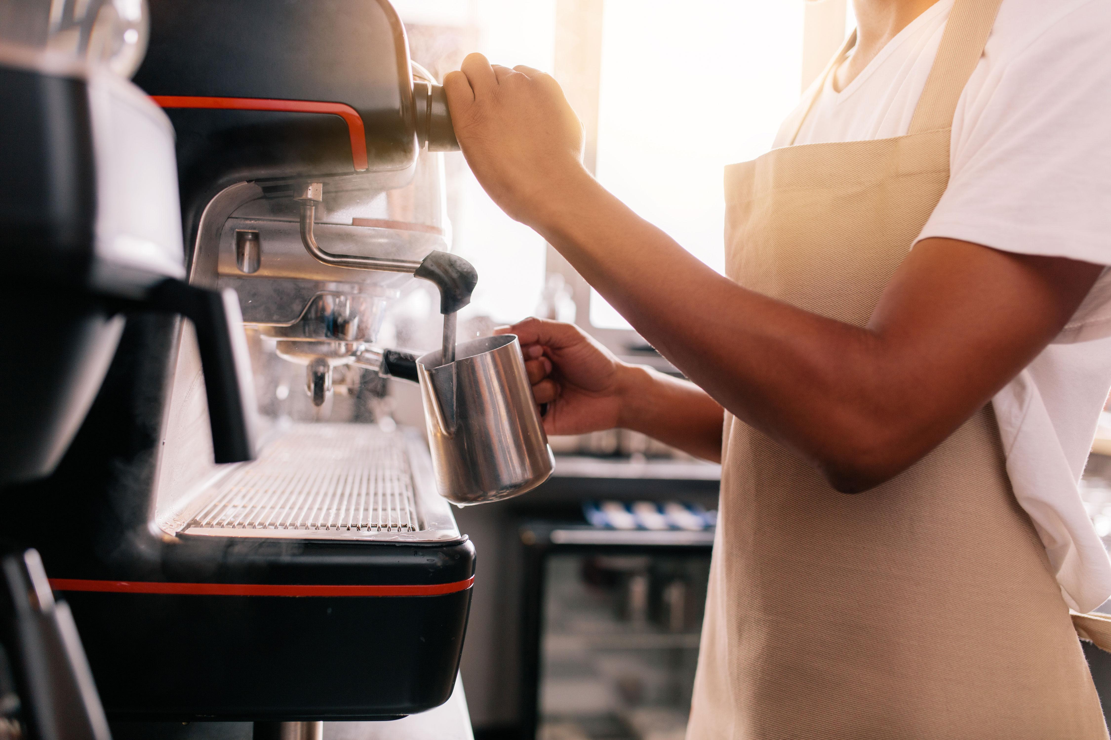 Barrista macht Milchschaum an Kaffeemaschine im Café