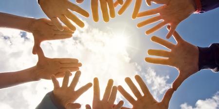 Zusammengeführte Hände im Kreis in der Sonne