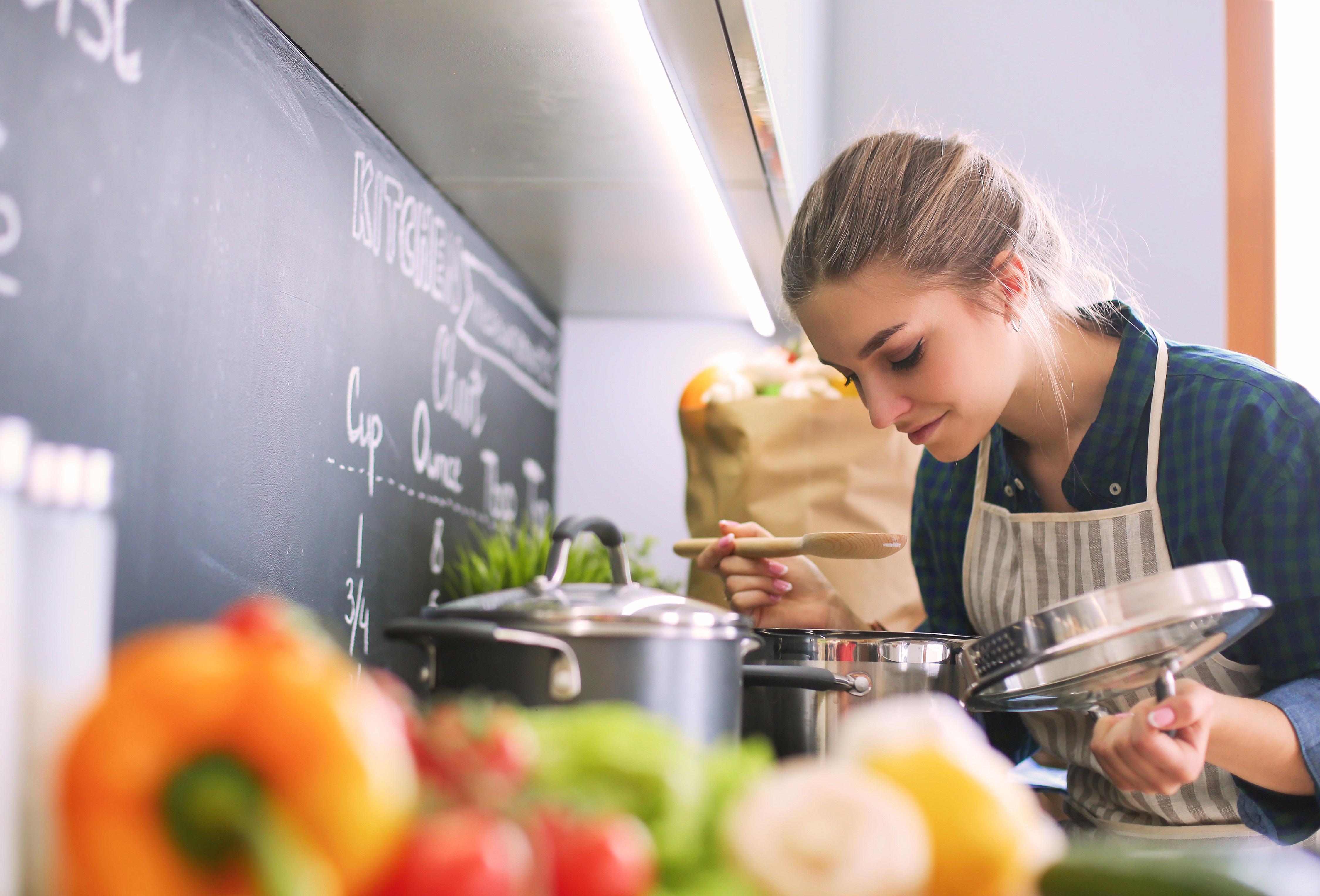 Junge Frau steht am Herd in ihrer Küche