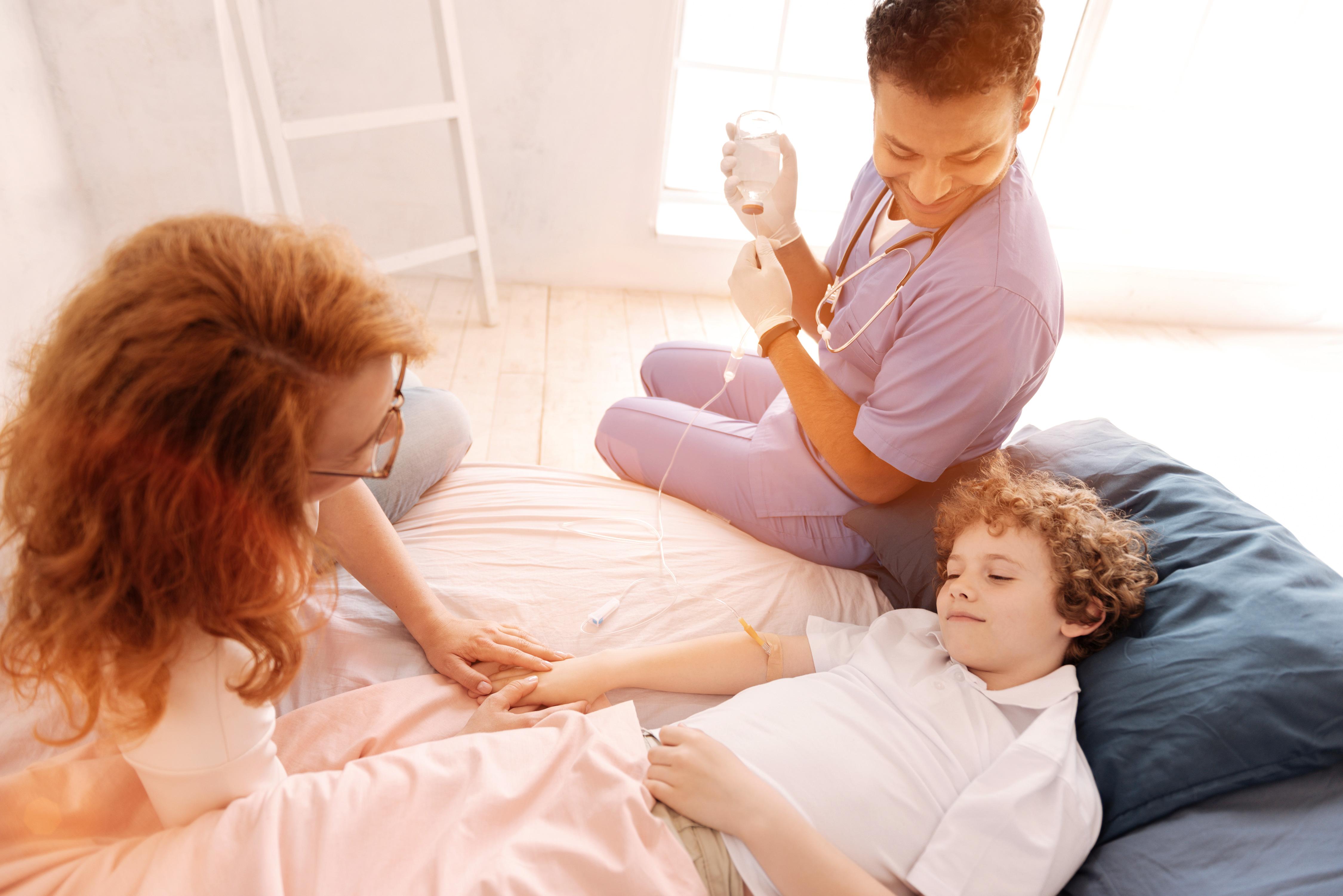 Lächelnder Arzt bei krankem Kind und seiner Mutter daheim