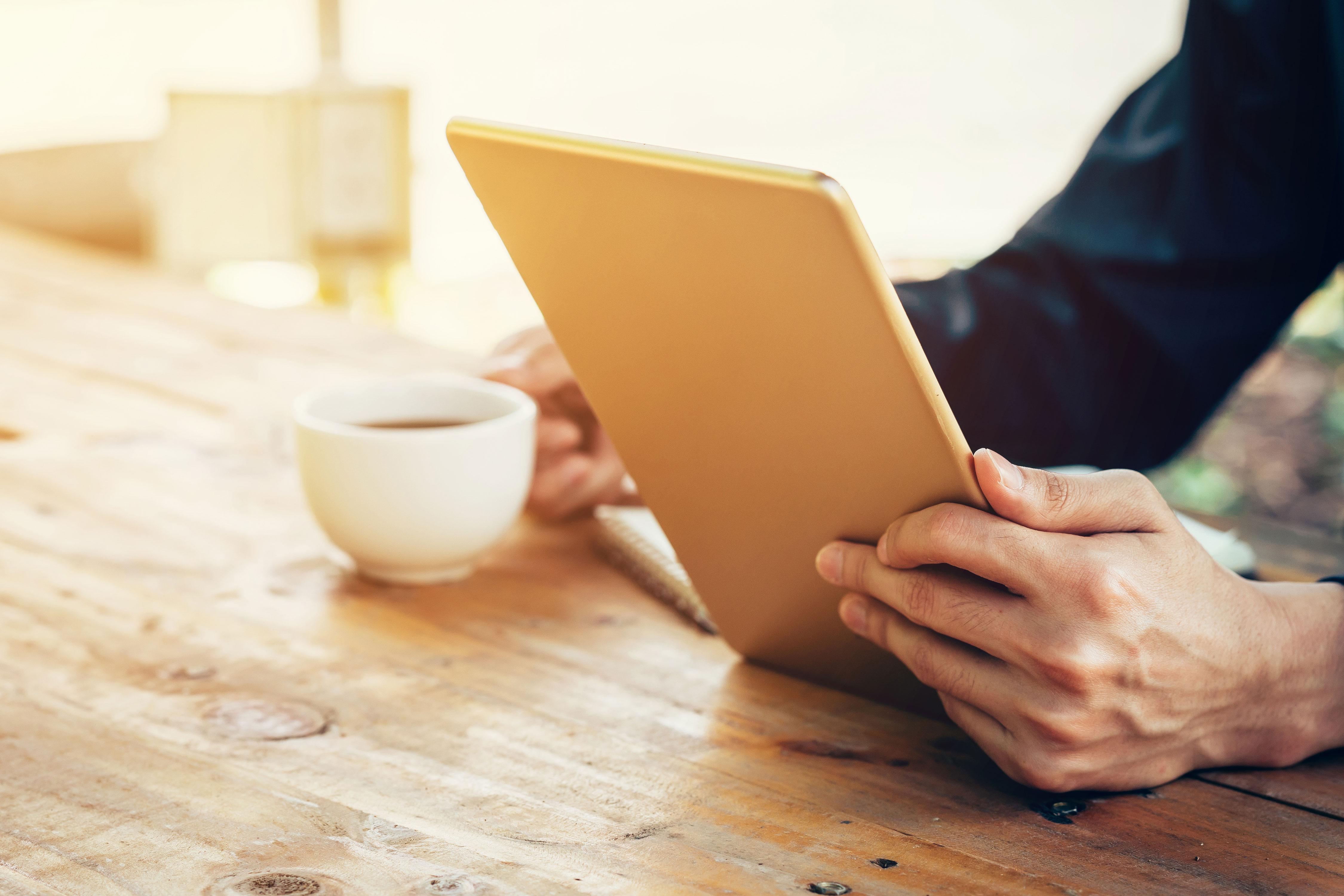 Businessman mit Tablet und Kaffeetasse an Holztisch im Café