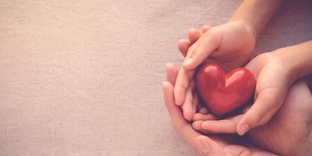 Vater und Sohn halten ein rotes Herz in den Händen