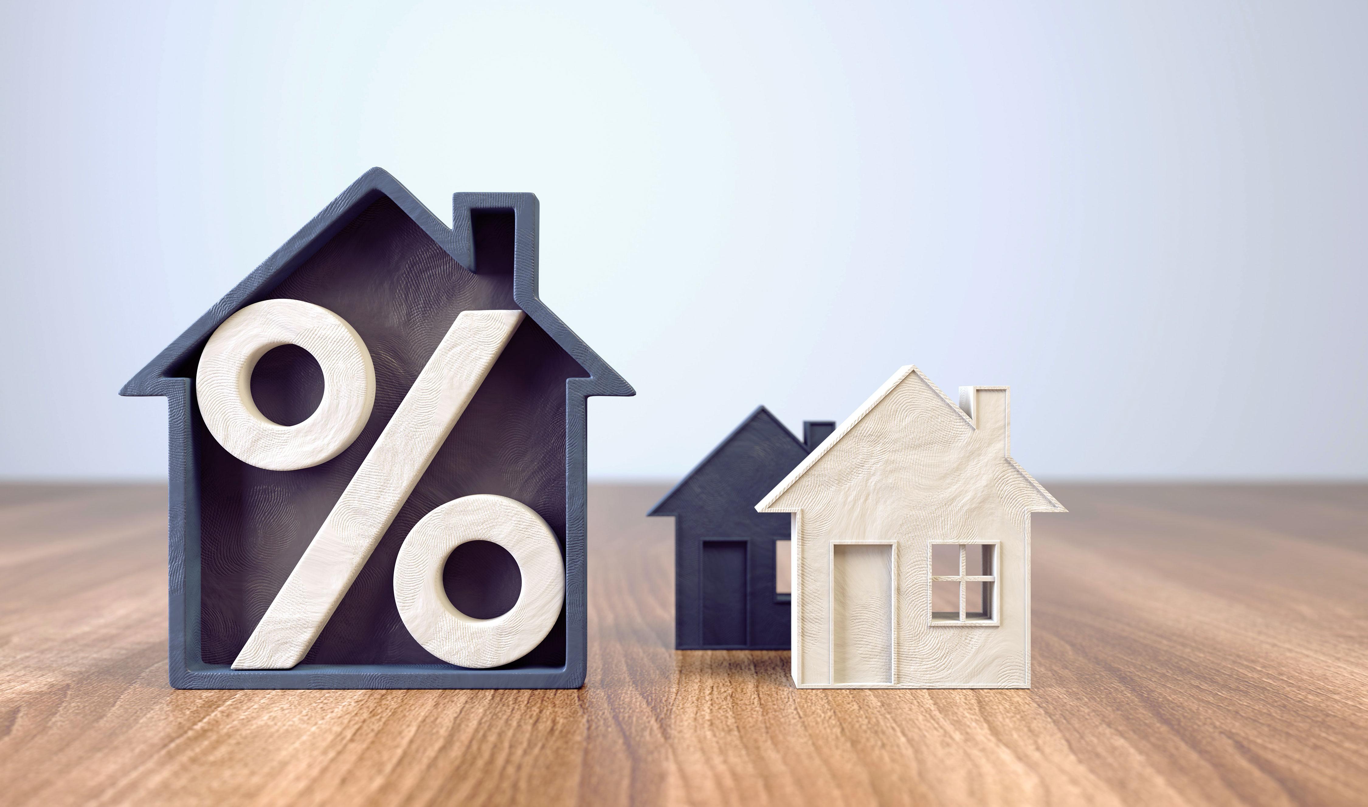 Immobilienzinsen dargestellt mit einfachen Hausmodellen aus Holz