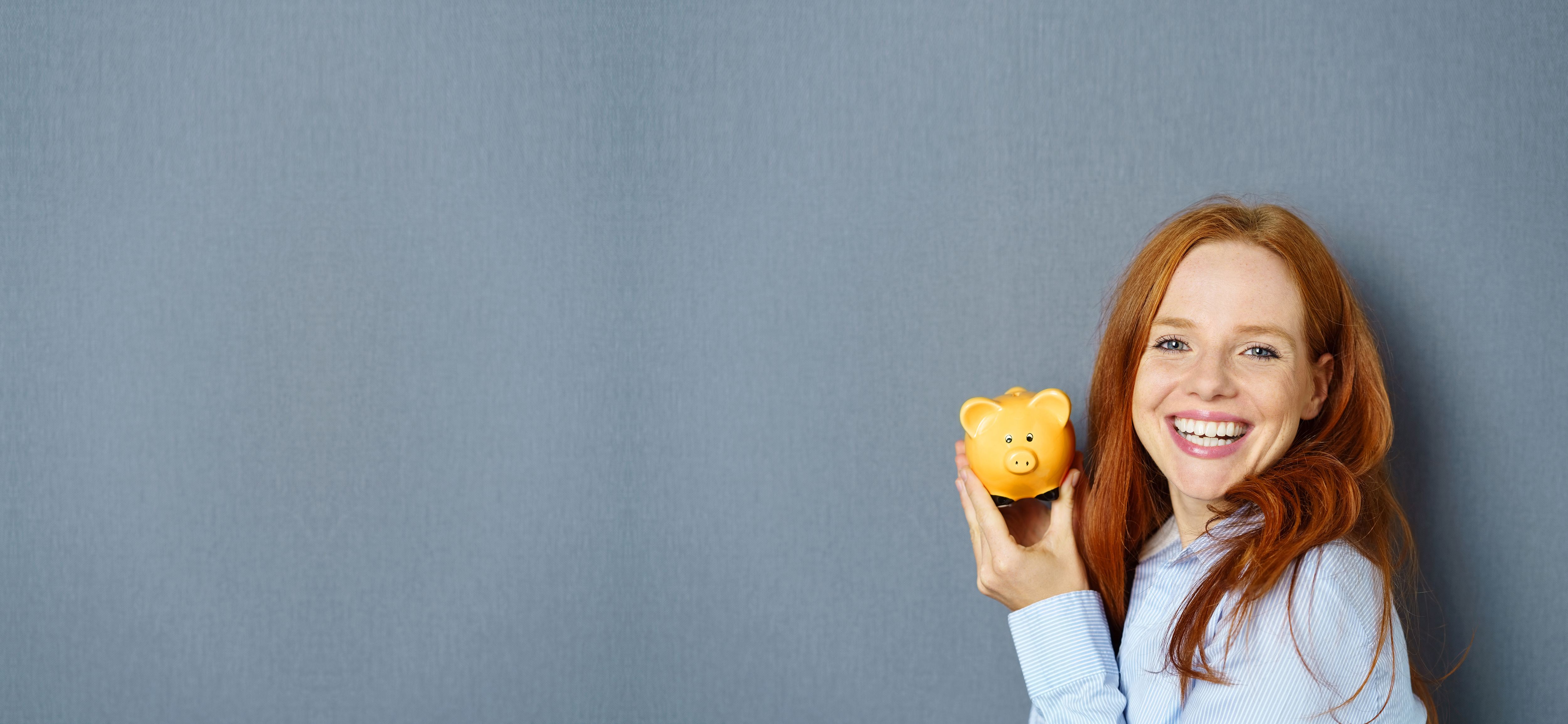 Aktionsbonus Energie - rothaarige Frau mit orangem Sparschwein