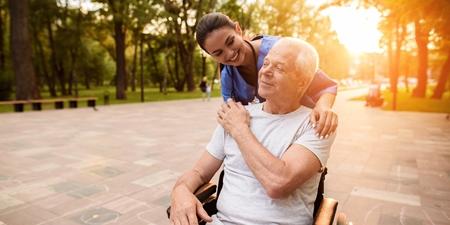 Mann sitzt im Rollstuhl und wird von Pflegerin versorgt