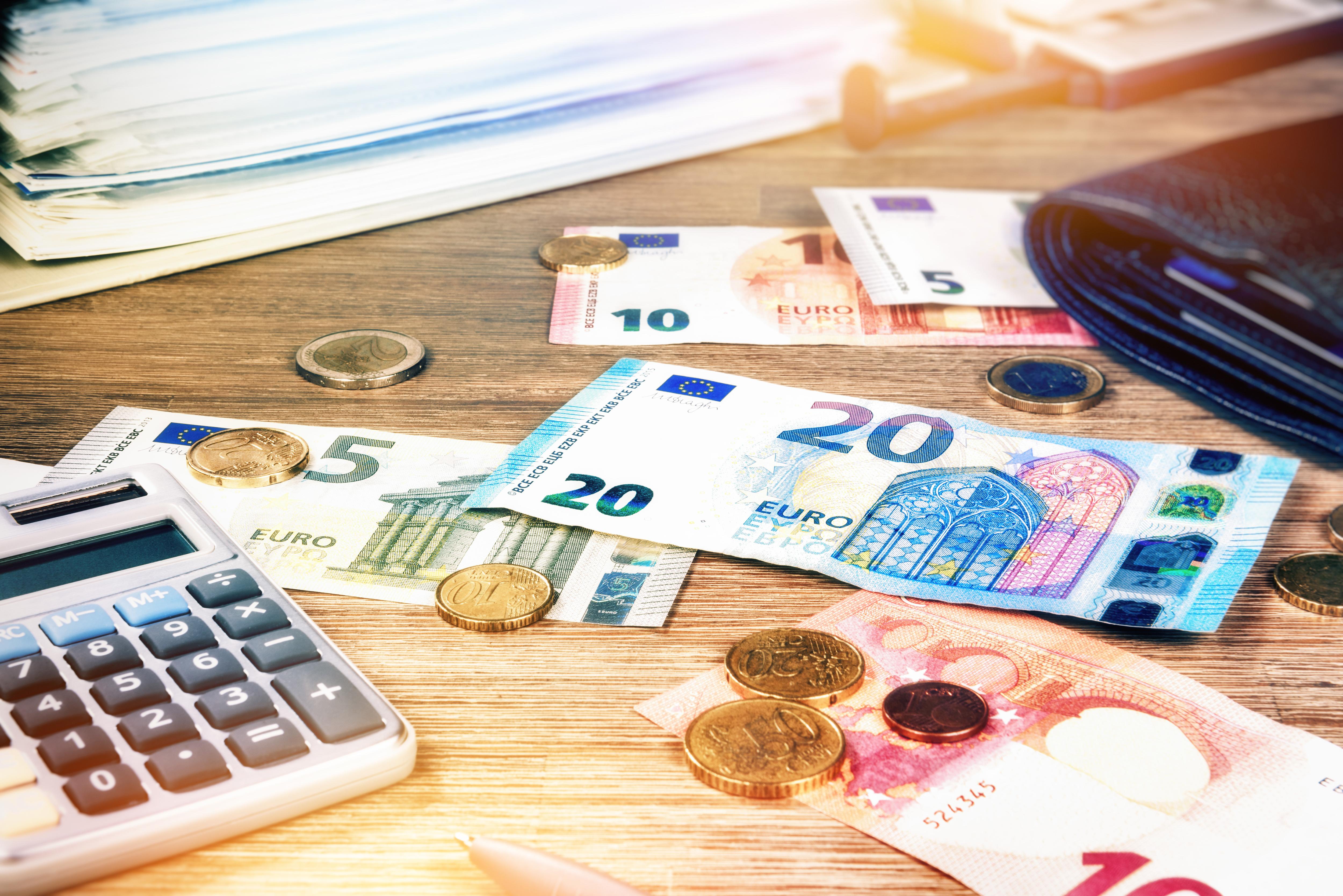 Euro-Banknoten und -münzen auf Holztisch neben Taschenrechner, Geldbörse und Aktenordner