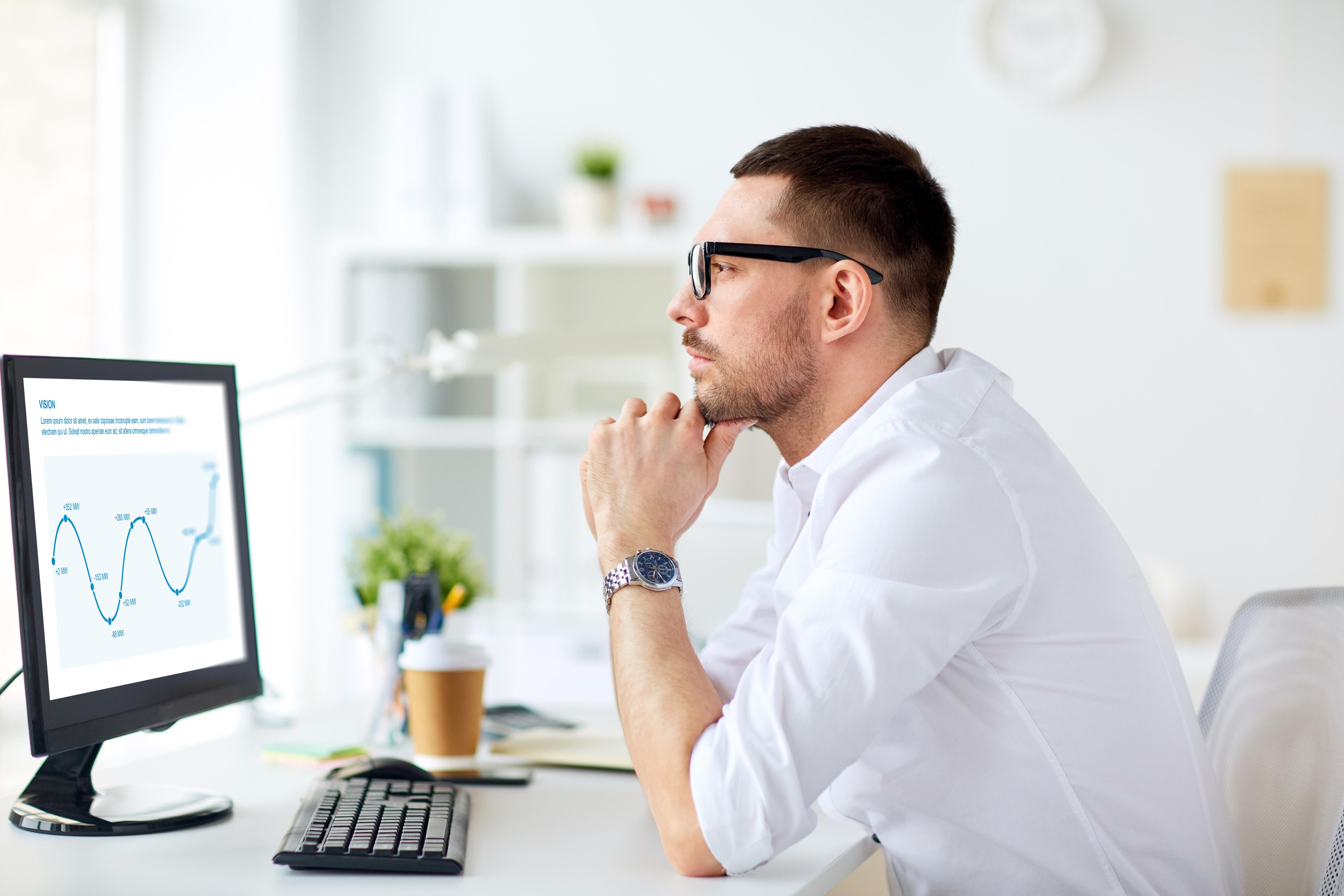 Geschäftsmann mit Tablle am Computer