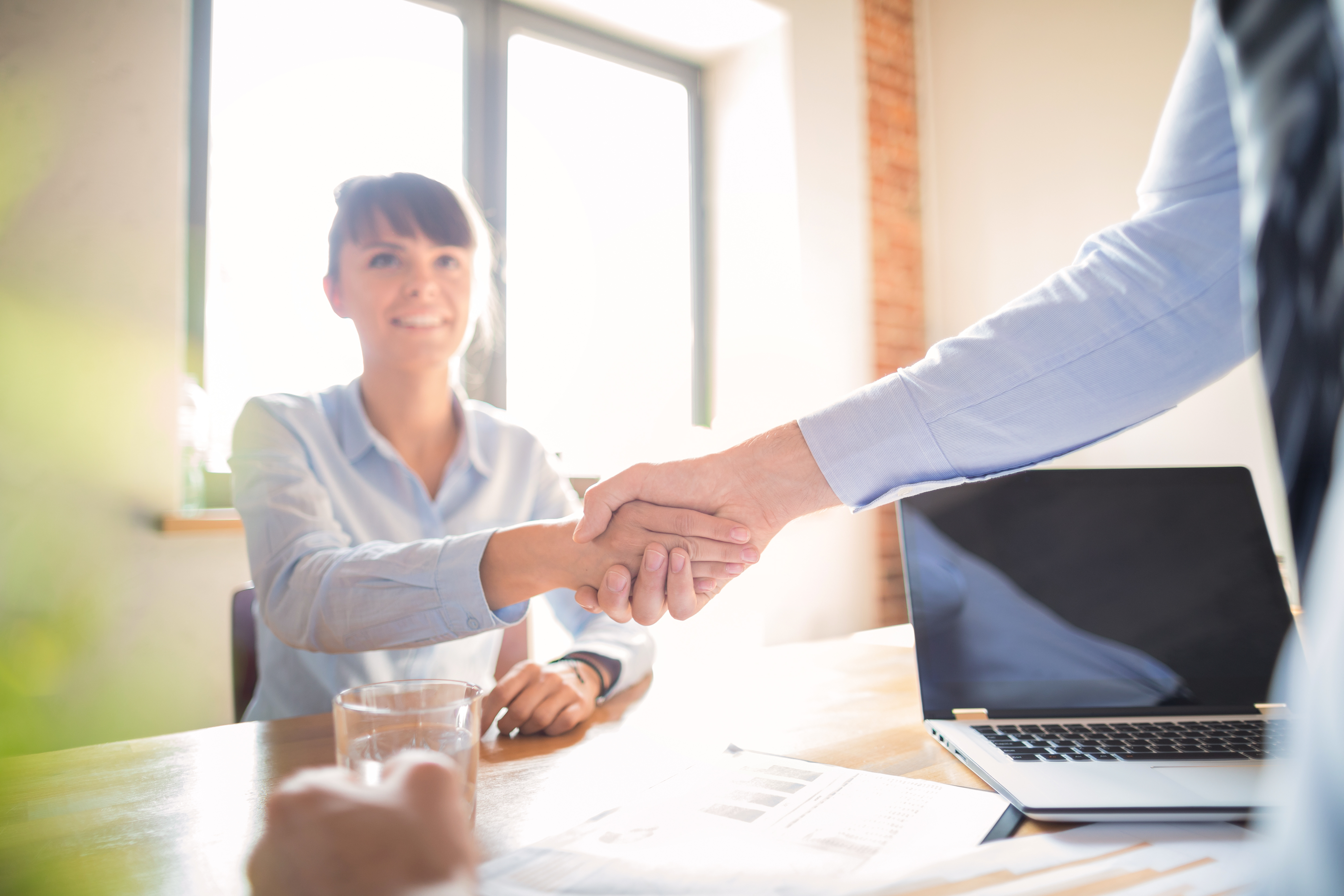 Handschlag zwischen Geschäftsleuten am Schreibtisch