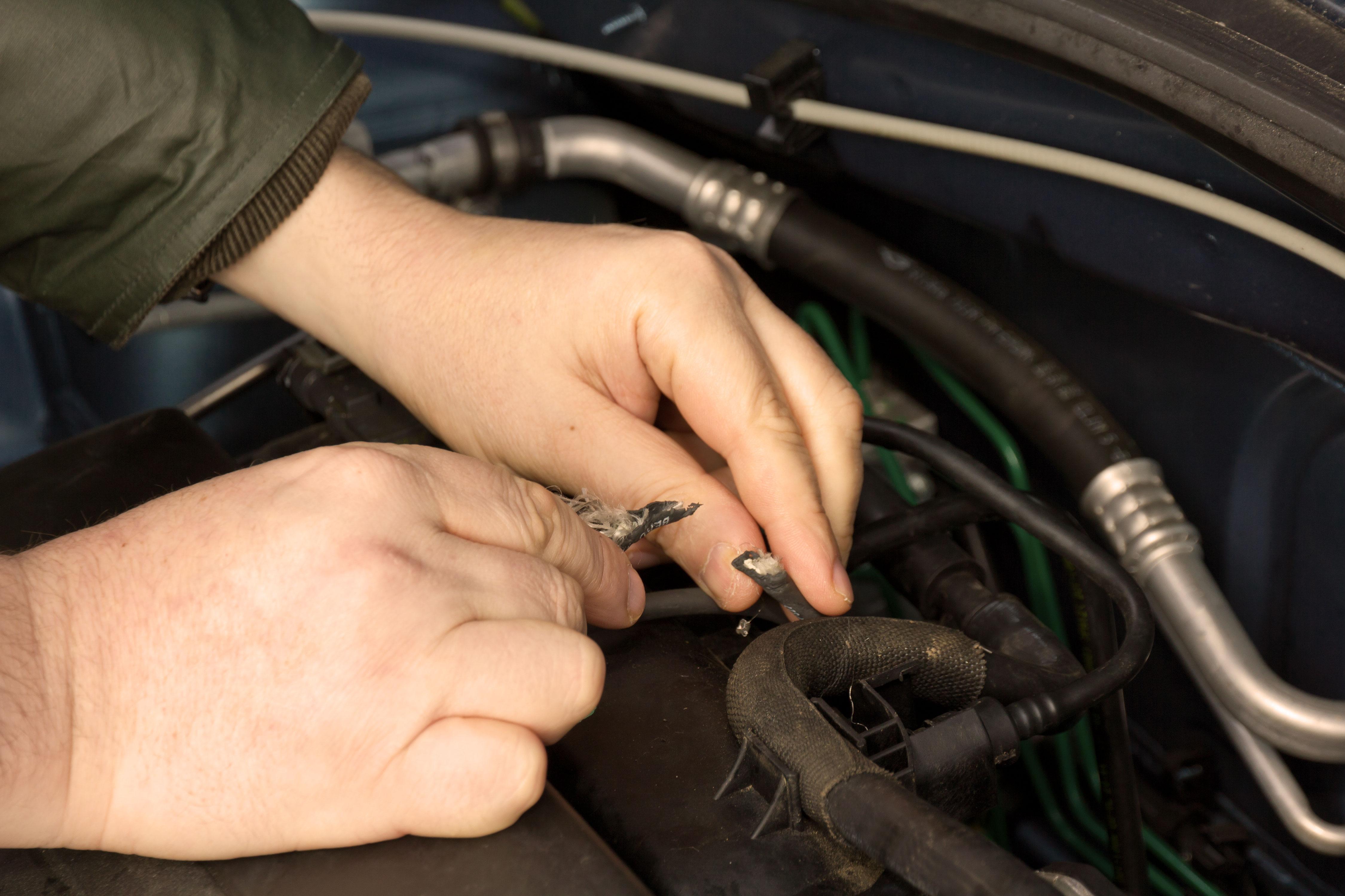 Hände untersuchen Marderschaden am Auto