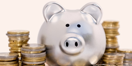 Stapel von Euromünzen vor silbernem Sparschwein