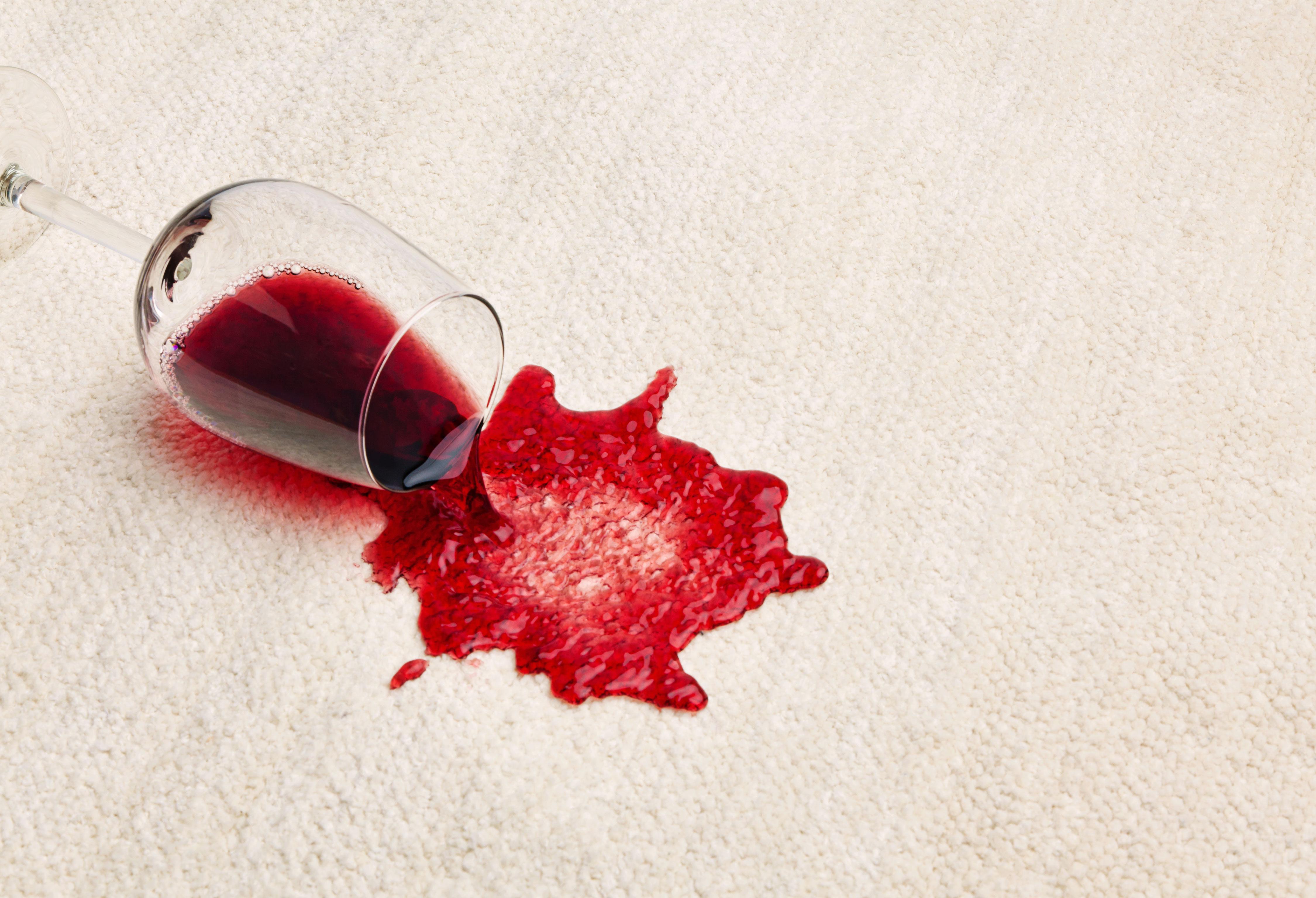Ausgeschüttetes Rotweinglas auf weißem Teppich
