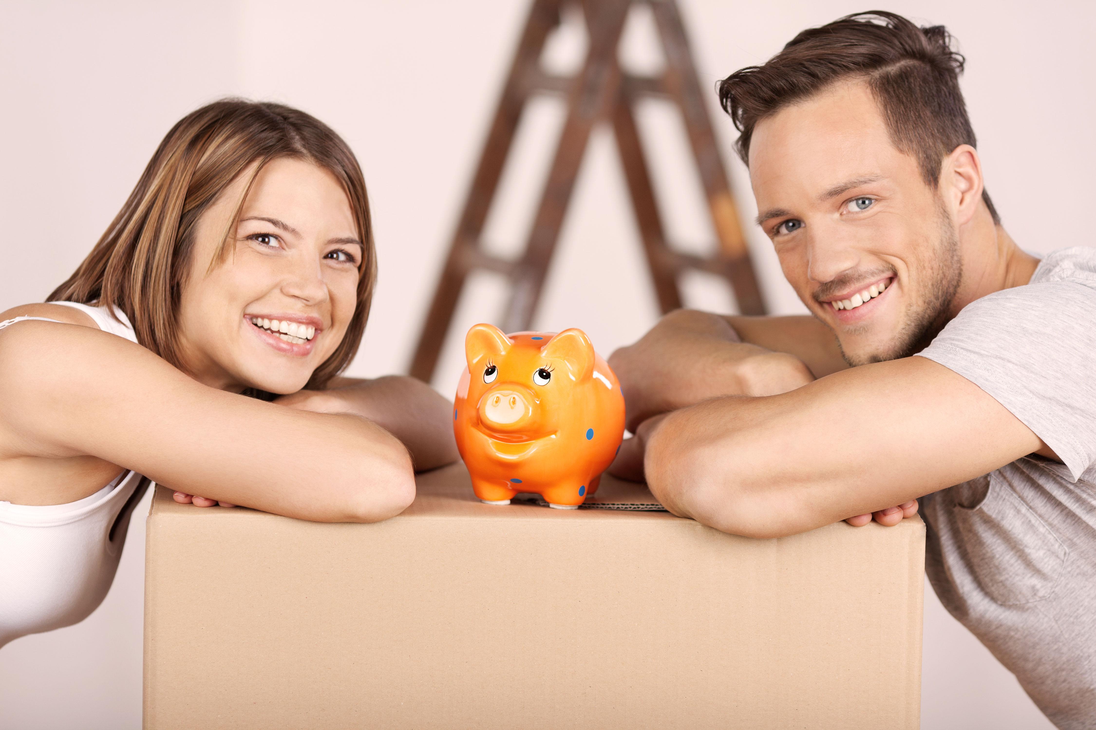 Paar mit Sparschwein und Umzugskarton