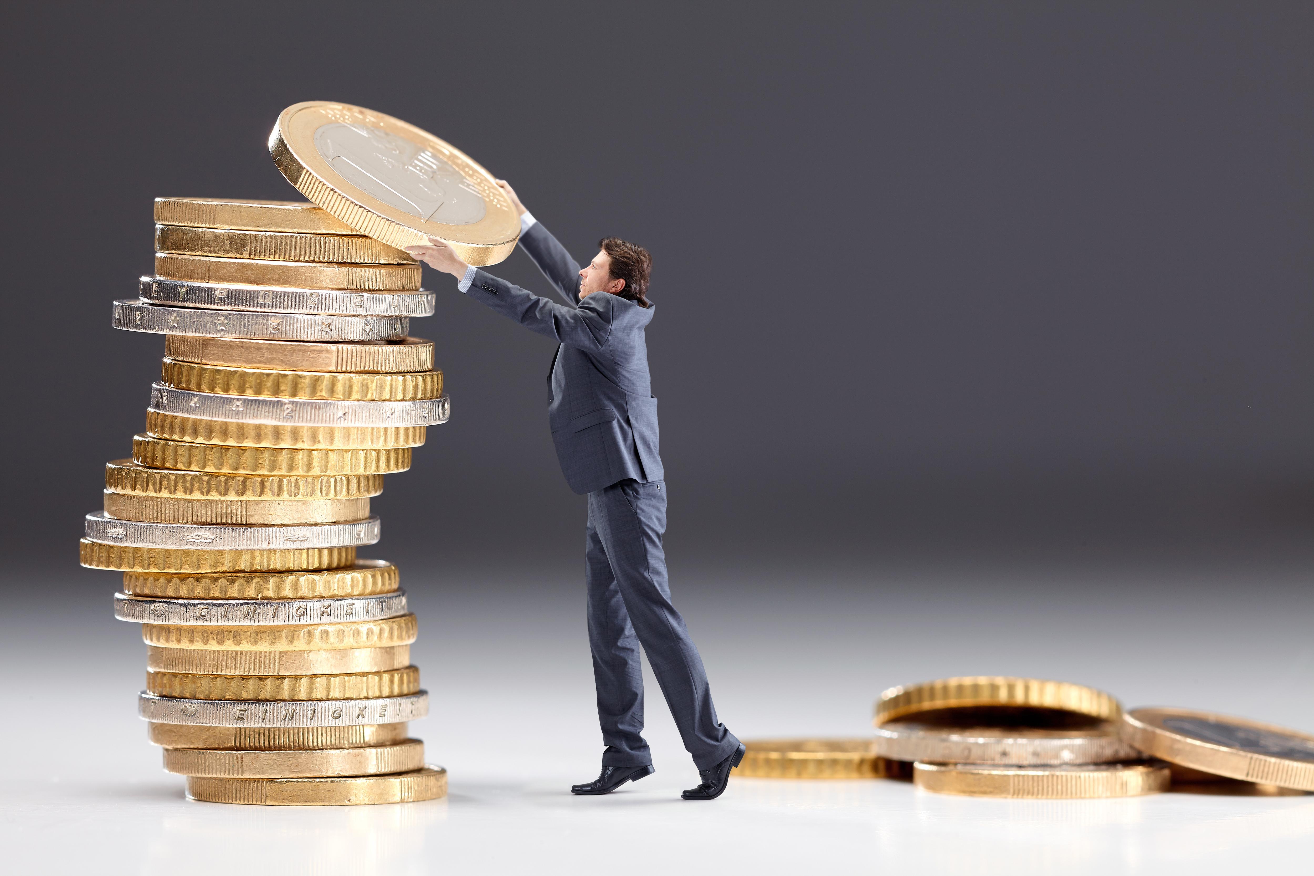 Man legt übergroße Münze auf Münzstapel
