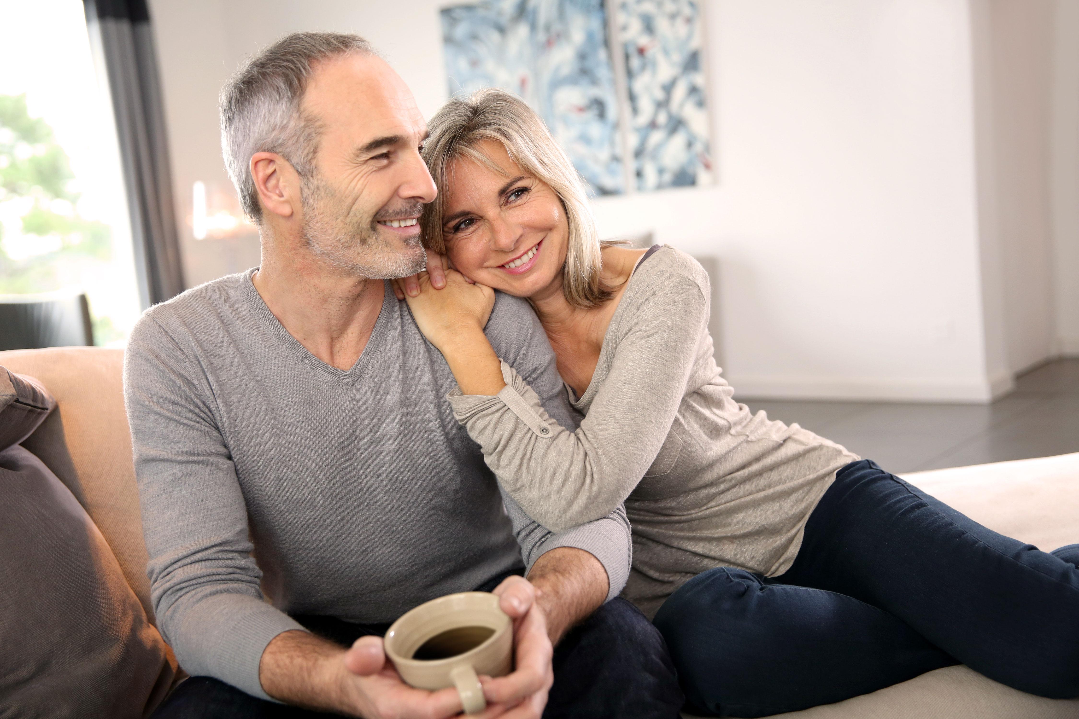 Lächelndes älteres Paar auf der Couch sitzend