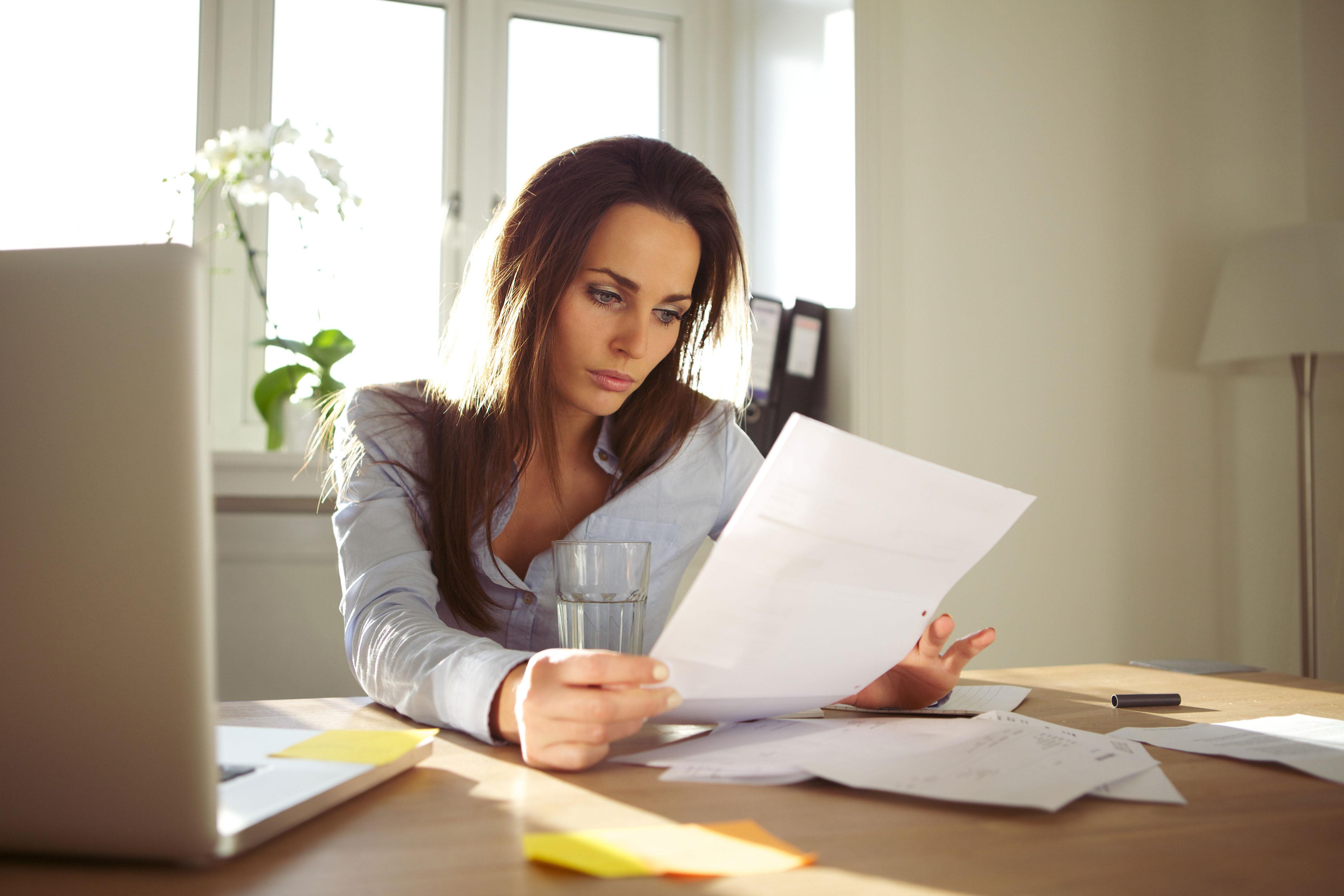 Frau liest Dokument am Schreibtisch