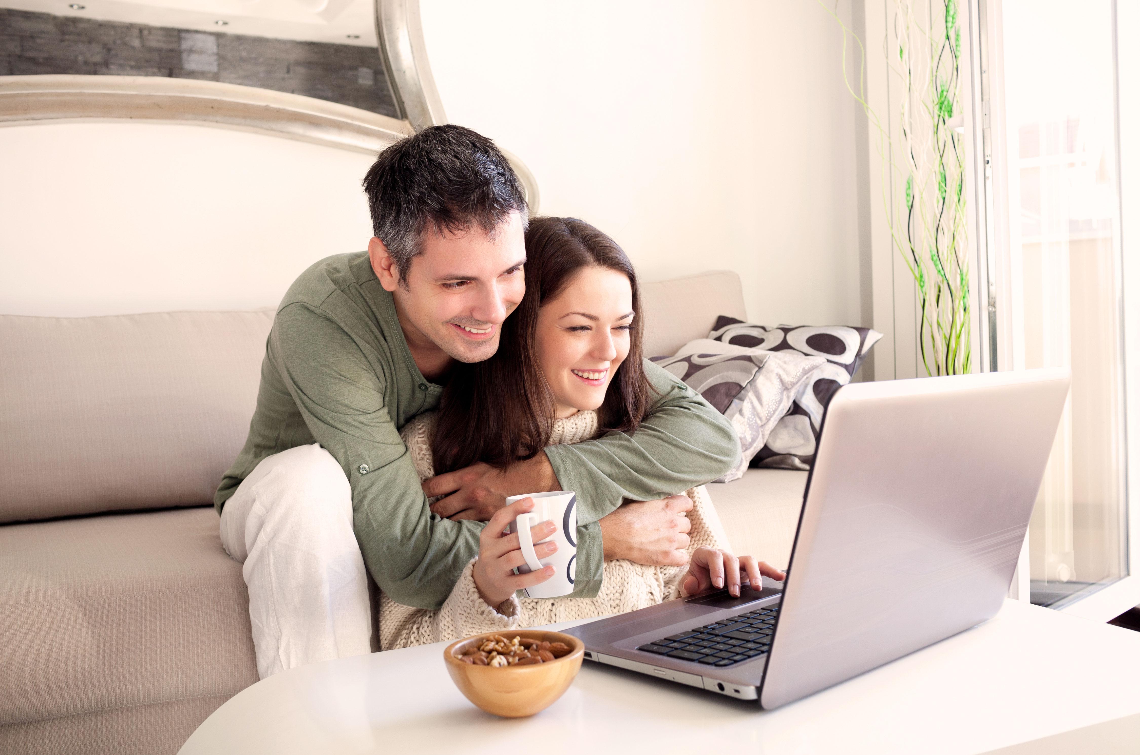 Junges lächelndes Paar in Umarmung vor dem Laptop