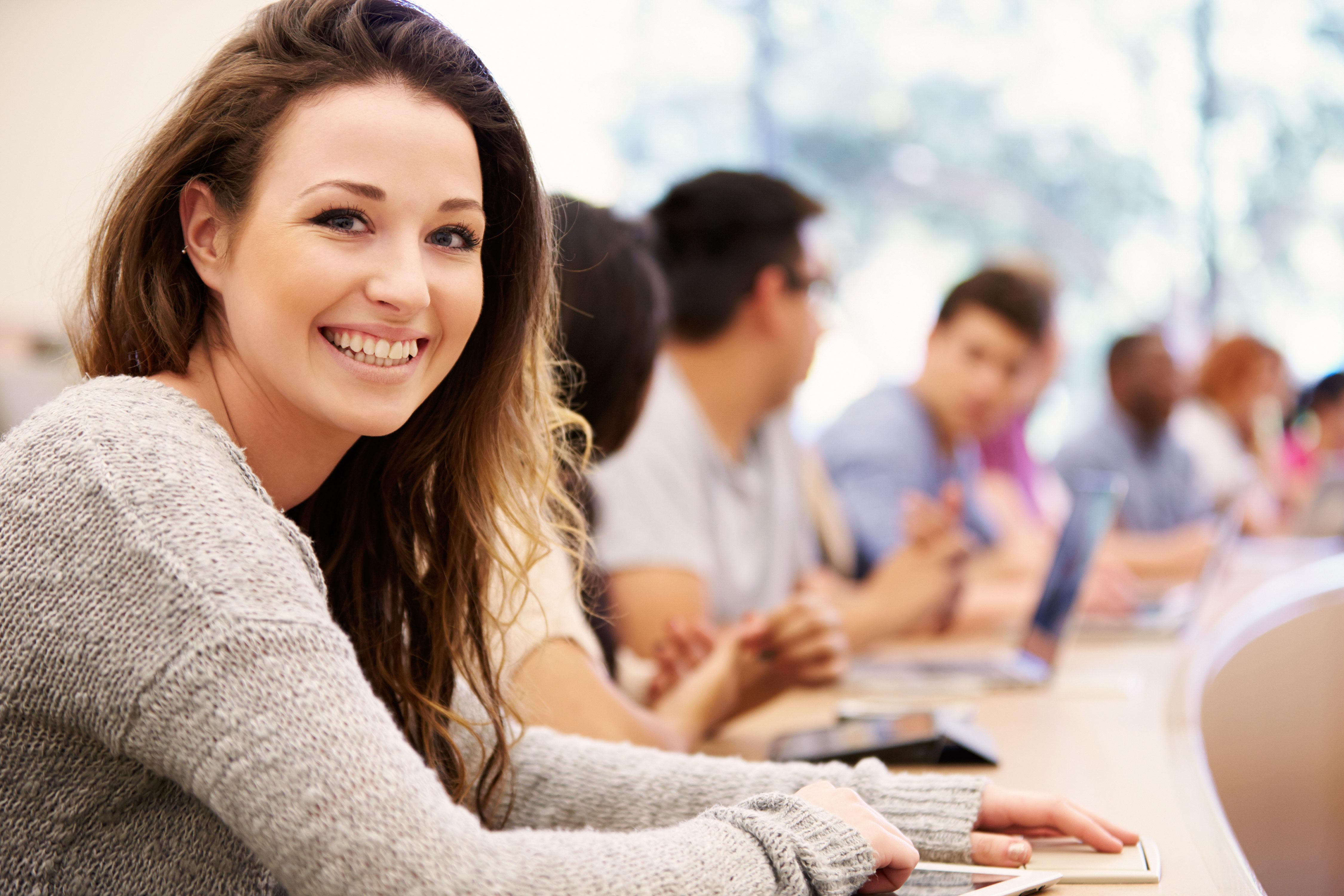 Junge lächelnde Studentin in Vorlesung mit Tablet