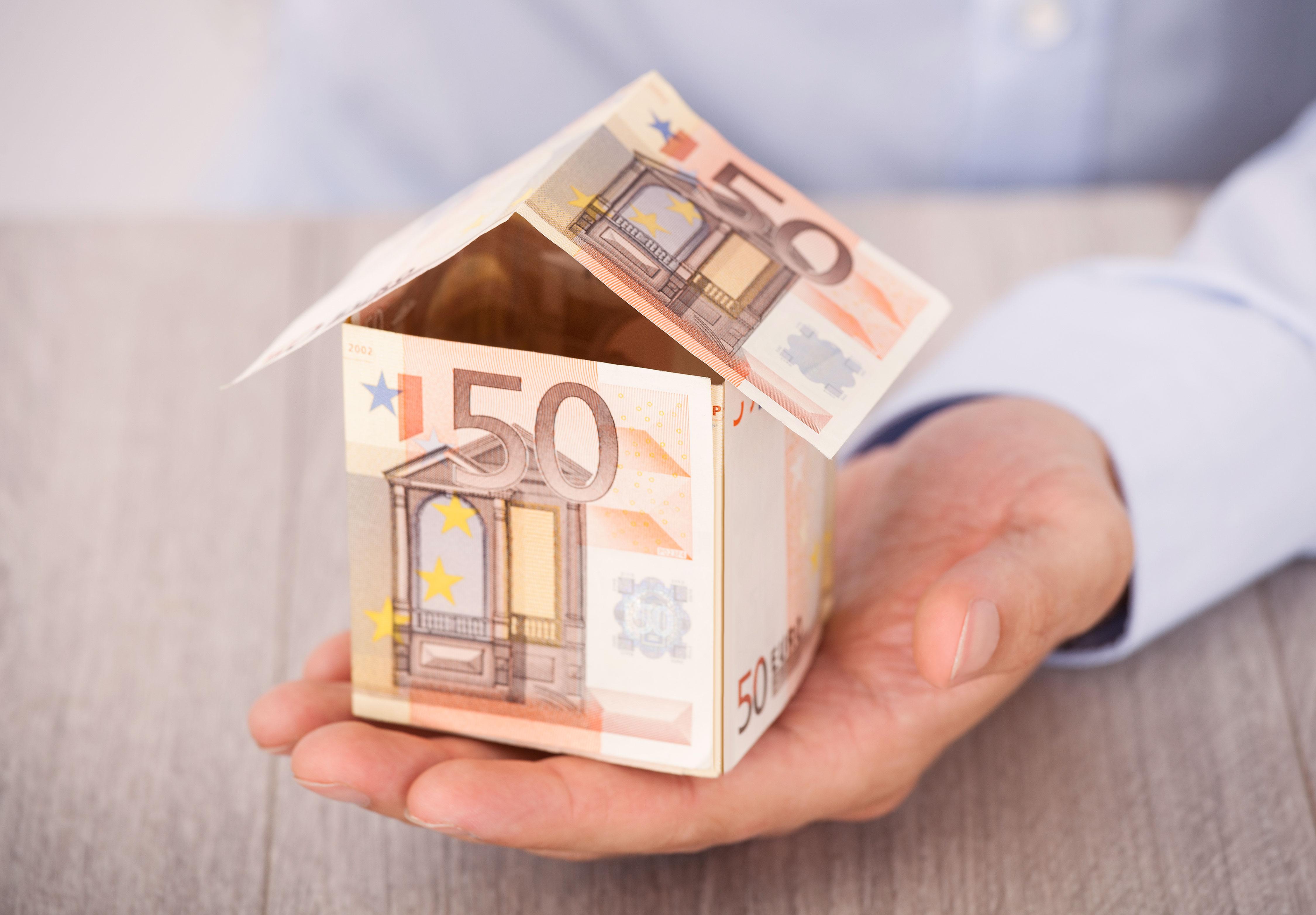 Businessman hält Haus aus Fünfzigeuroscheinen in seiner offenen Hand