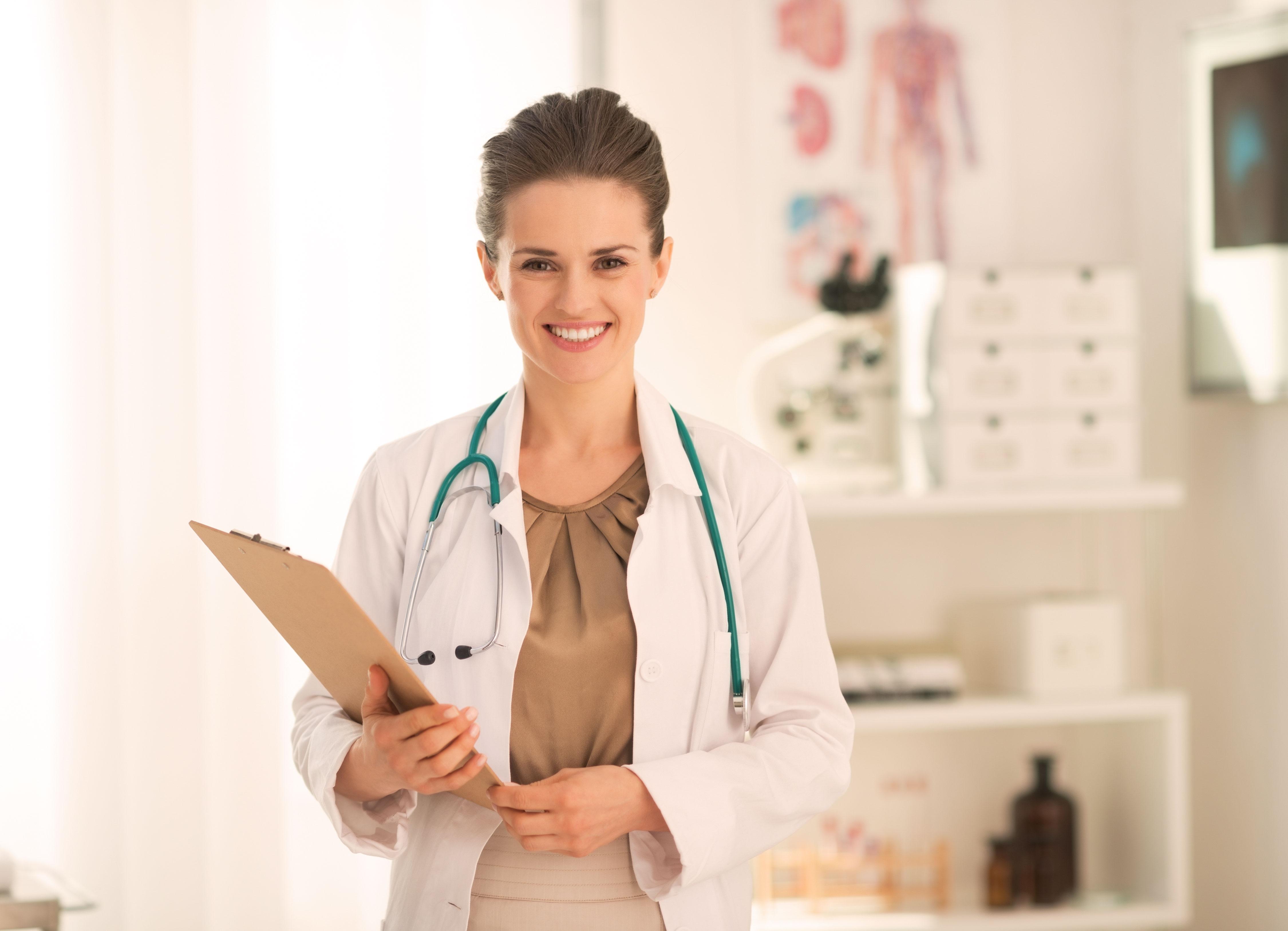 Lächelnde Ärztin mit Klemmbrett und Stethoskop