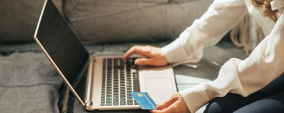 Junge Frau mit Kreditkarte im Close-up vor dem Laptop