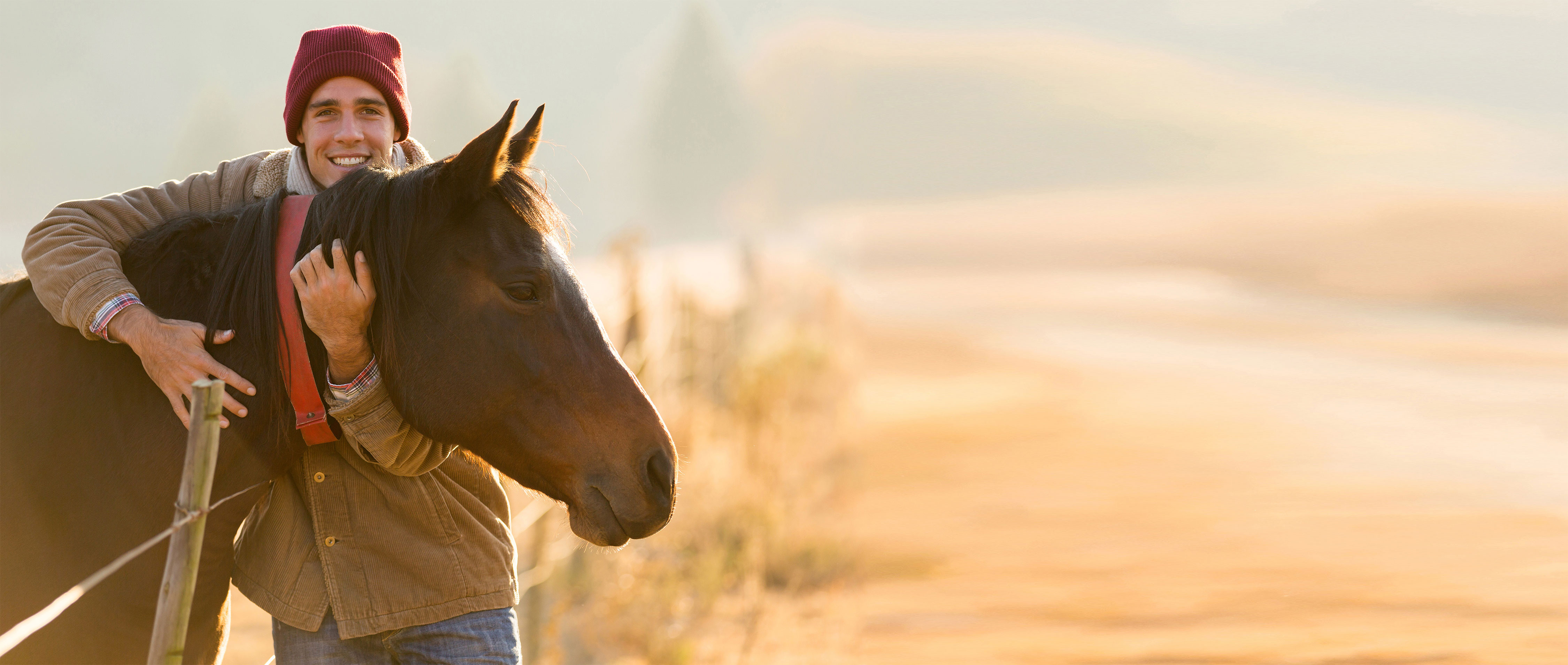 Junger Mann umarmt sein Pferd in der Natur