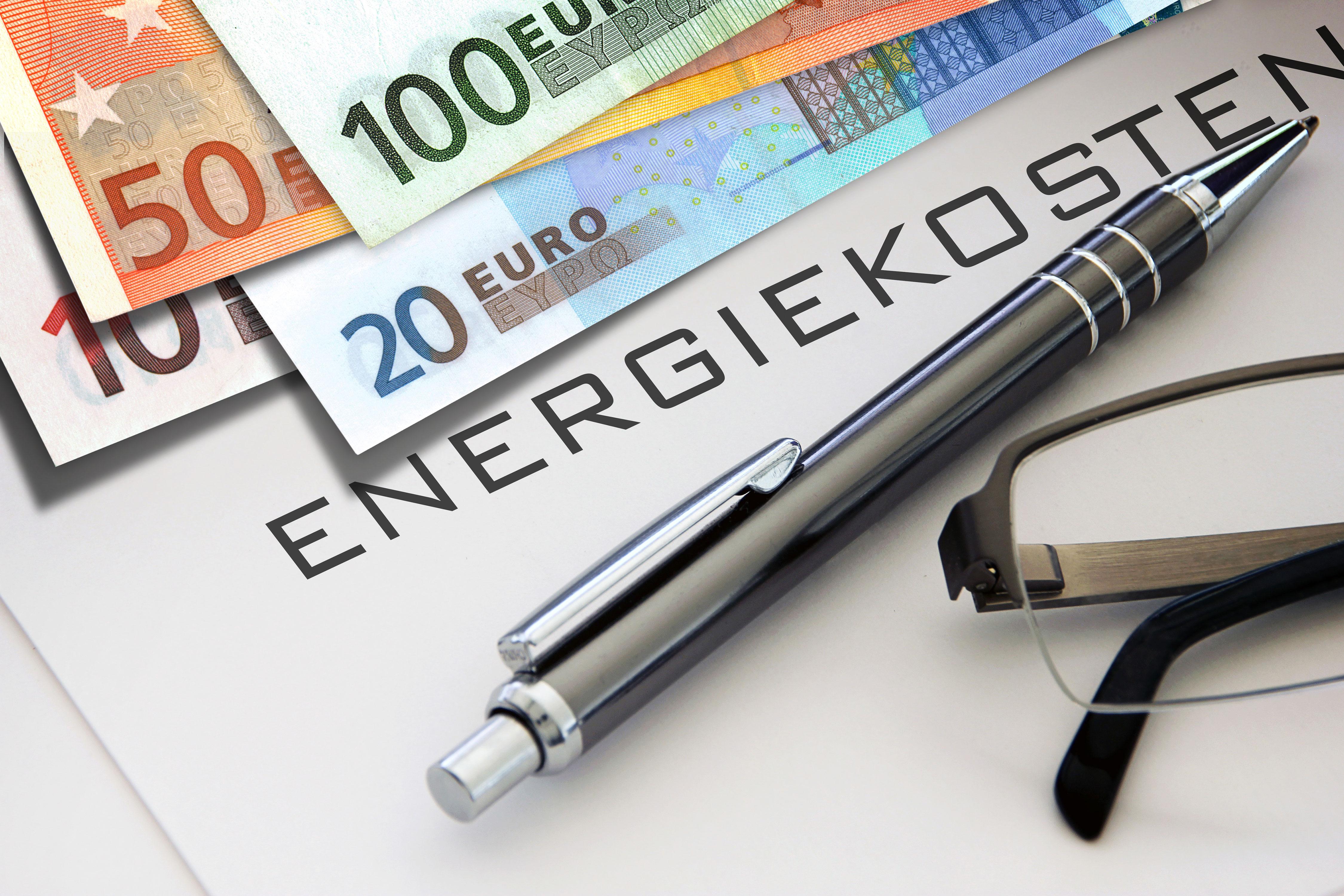 Kugelschreiber, Brille und Geldscheine auf Dokument mit Schriftzug Energiekosten