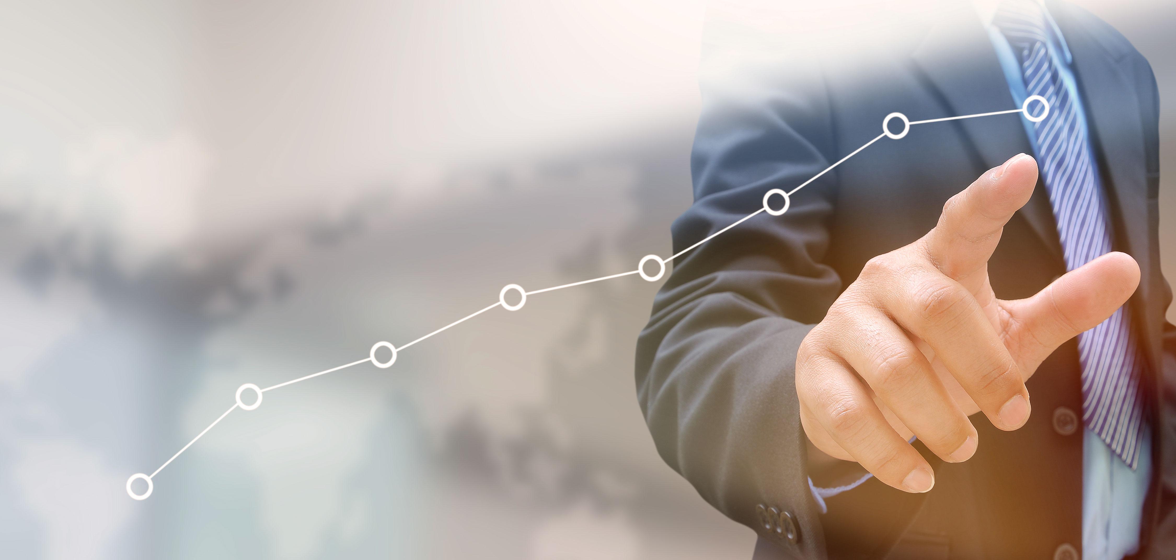 Businessman zeigt mit der Hand auf Grafik auf Touchscreen