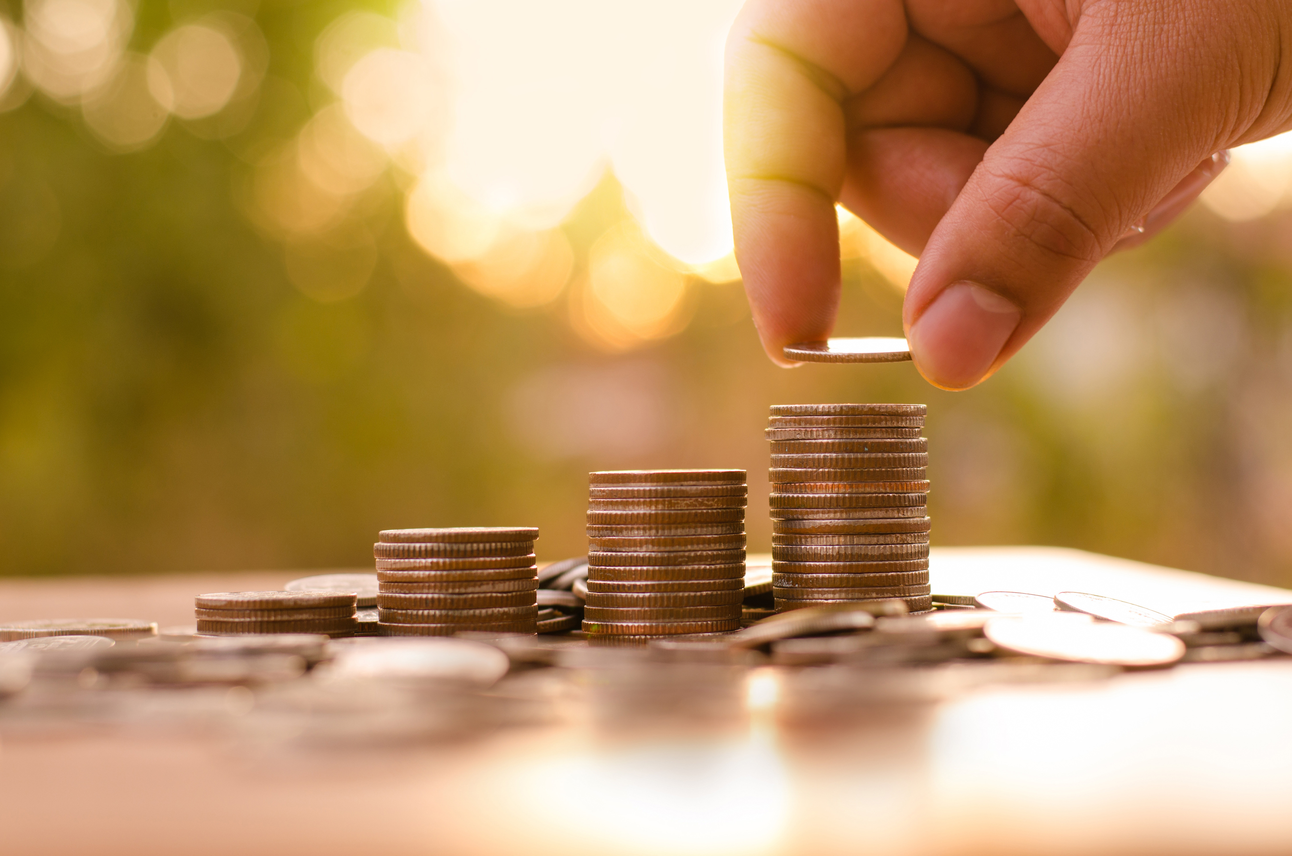 Hand stapelt Münzen auf Tisch im Garten